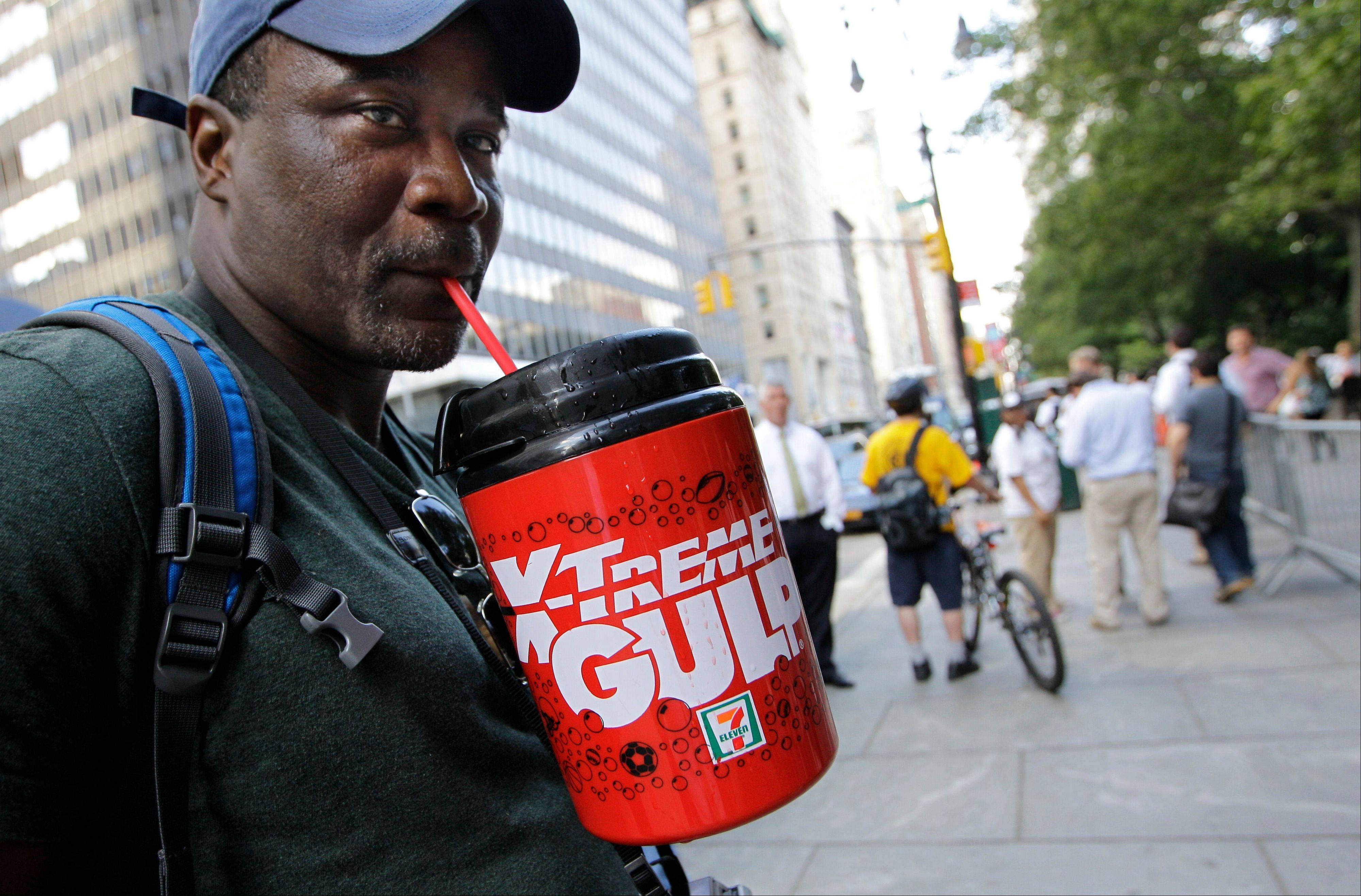 In this July photo, protester Eric Moore sips on an extra-large beverage during a protest against Mayor Michael Bloomberg's proposal to prohibit licensed food establishments from using containers larger than 16 ounces to serve high-calorie drinks at City Hall in New York. The era of the supersized cola may come to an end in New York City on Thursday, Sept. 13, 2012, when health officials are expected to approve the 16-ounce limit.