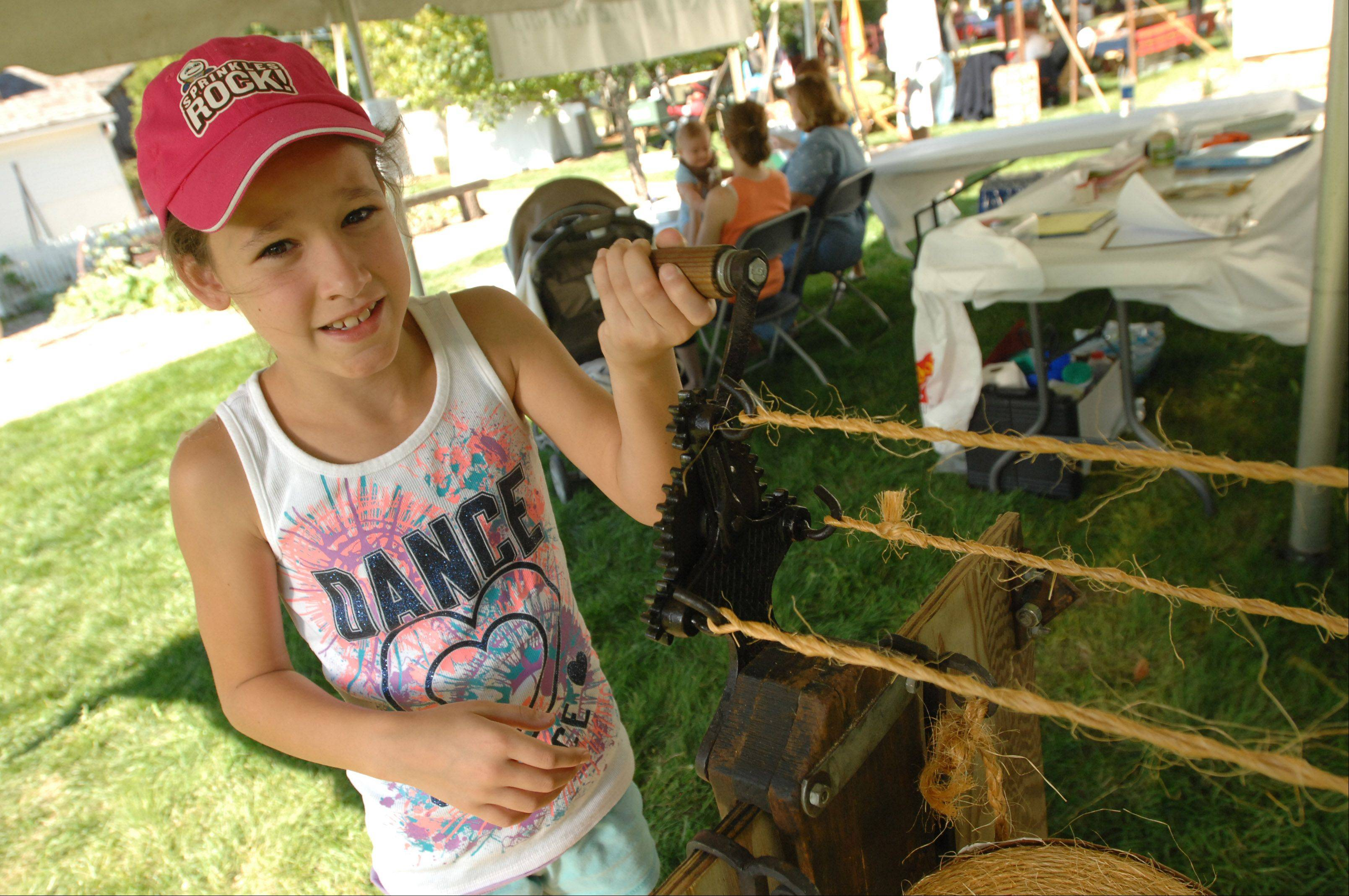 Teagan Pahl of Lisle makes rope Saturday during Depot Days in Lisle. Visitors also could grind corn into cornmeal and watch a Civil War cannon-firing demonstration at the event, which continues from noon to 5 p.m. Sunday.