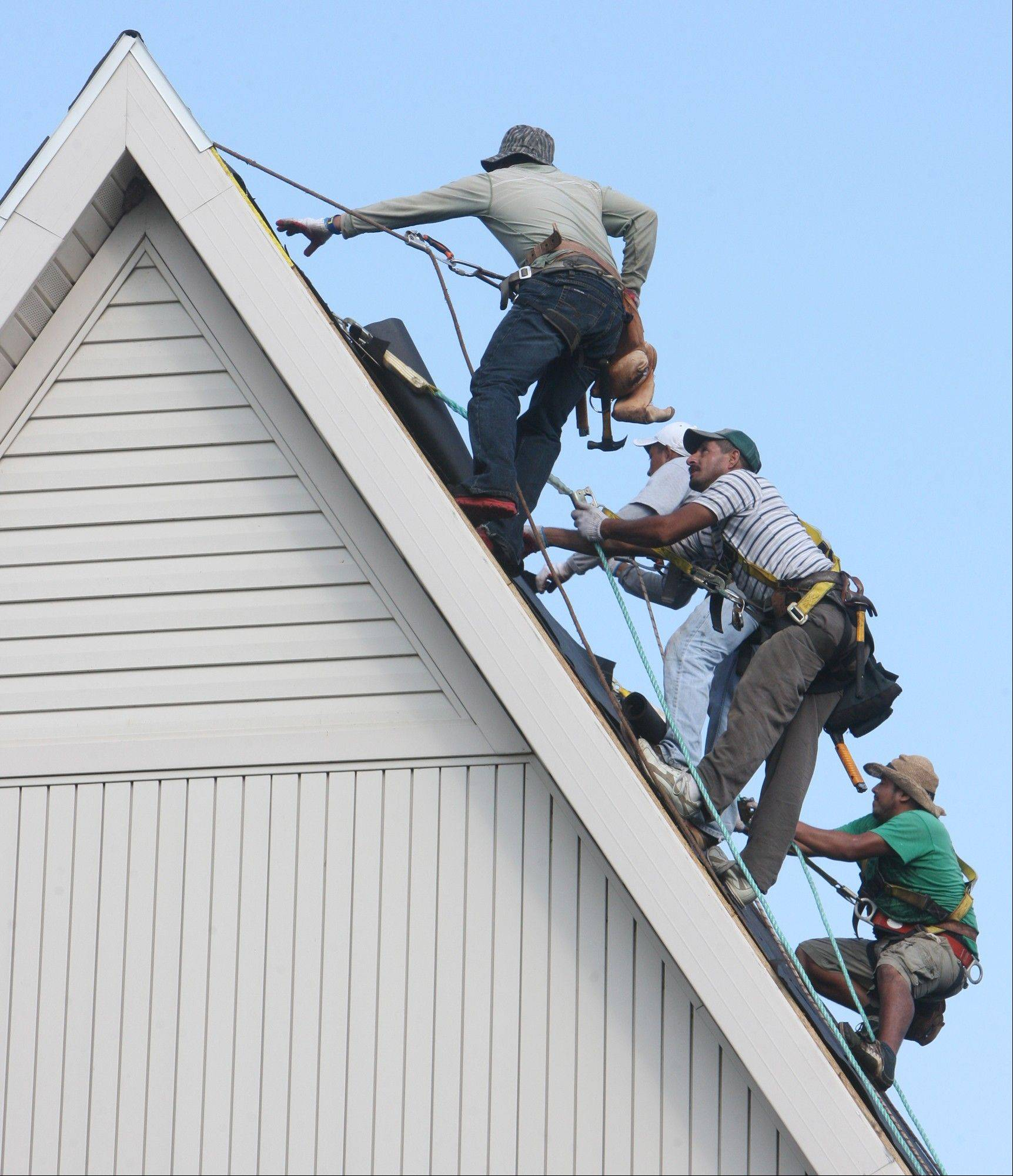 Four roofers were giving a peak performance Thursday as they rappel down from the peak of the First Christian Church, 760 Washington Avenue in Alton.