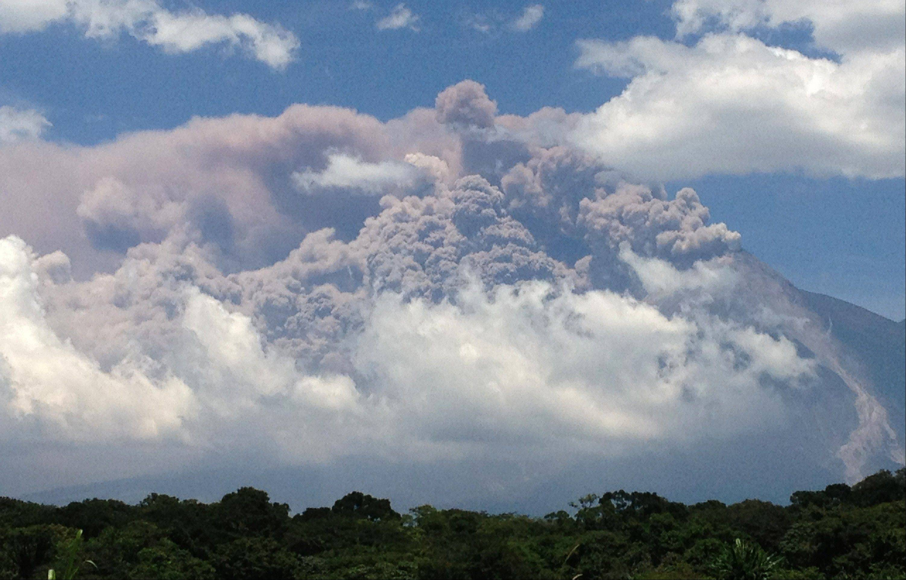 In this image from a cell phone, plumes of smoke rise from the Volcan de Fuego or Volcano of Fire as seen Thursday from Palin, south of Guatemala City.