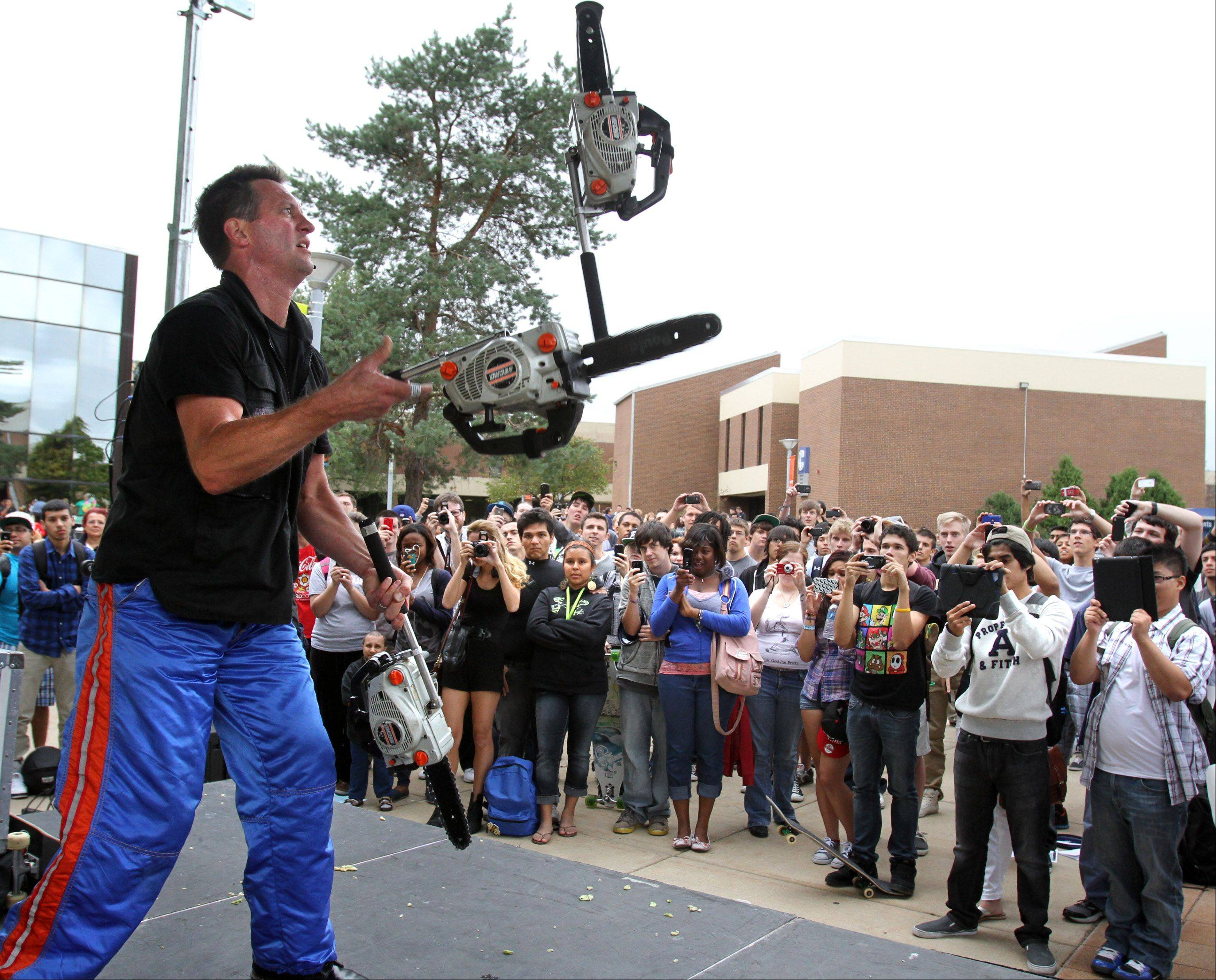 "Mad Chad Taylor juggles three chain saws while performing a 30-minute comedy juggling show during Harper College's Hullabaloo Thursday in Palatine. Taylor, a ""Guinness World Records"" holder, is known as the ""Evel Knievel of comedy,"" a reference to the famed daredevil motorcycle stunt man."