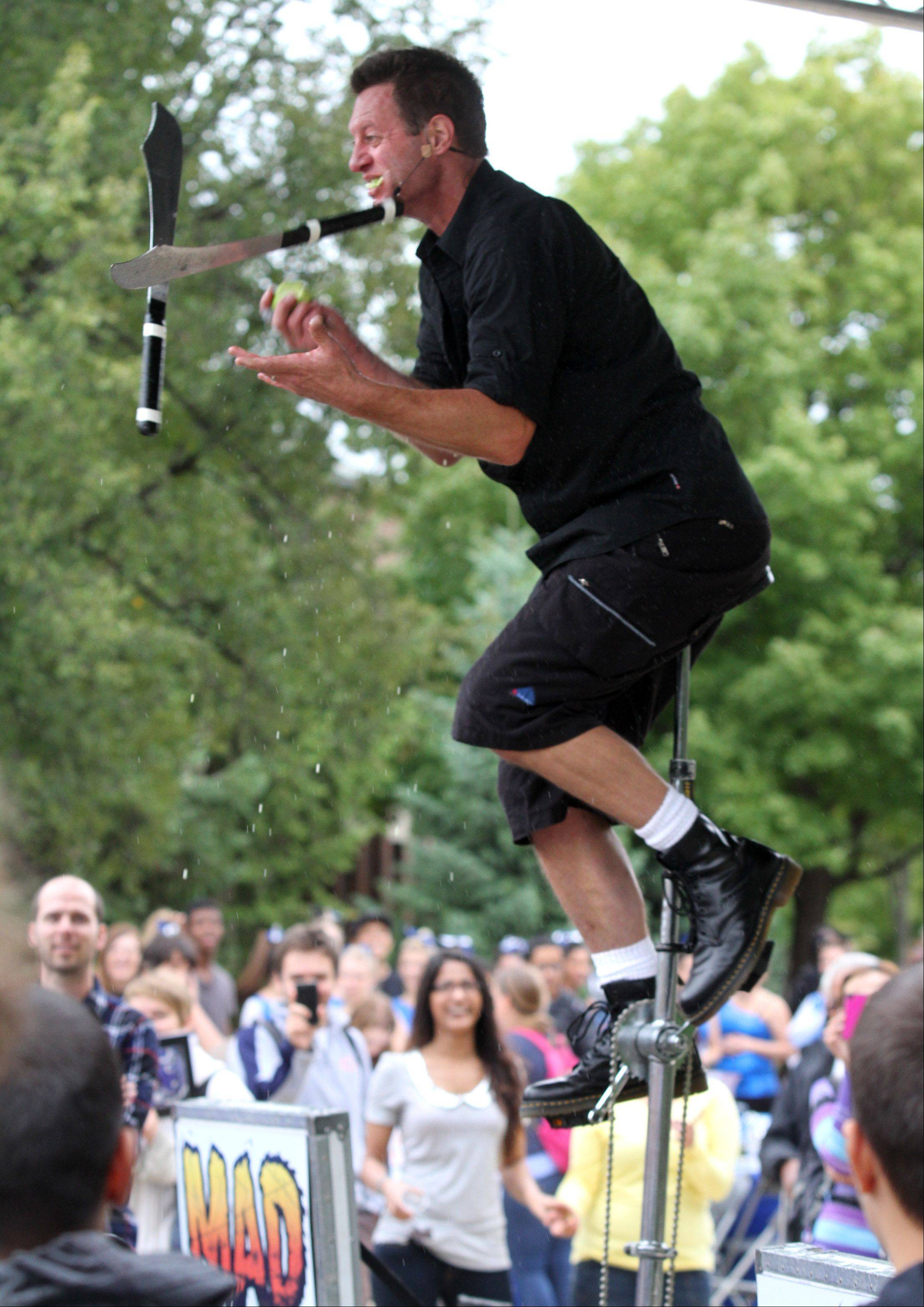 Mad Chad Taylor riding a unicycle juggles two-knifes and an apple while taking bites of the apples as he performs a 30-minute comedy juggling show during Harper College's Hullabaloo.