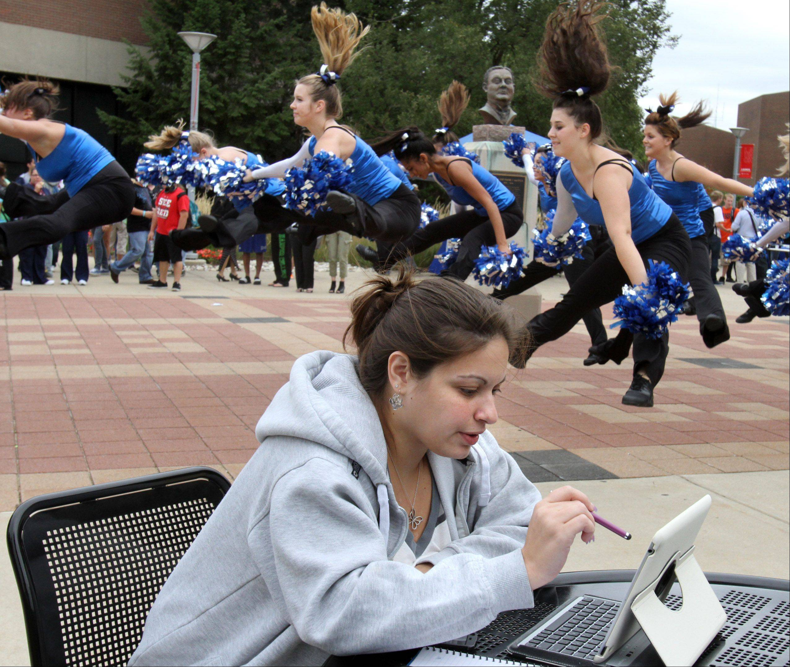 Jennifer Strang of Hoffman Estates studies math while the Harper College pom and dance team preforms at the college's Hullabaloo celebration on Thursday.