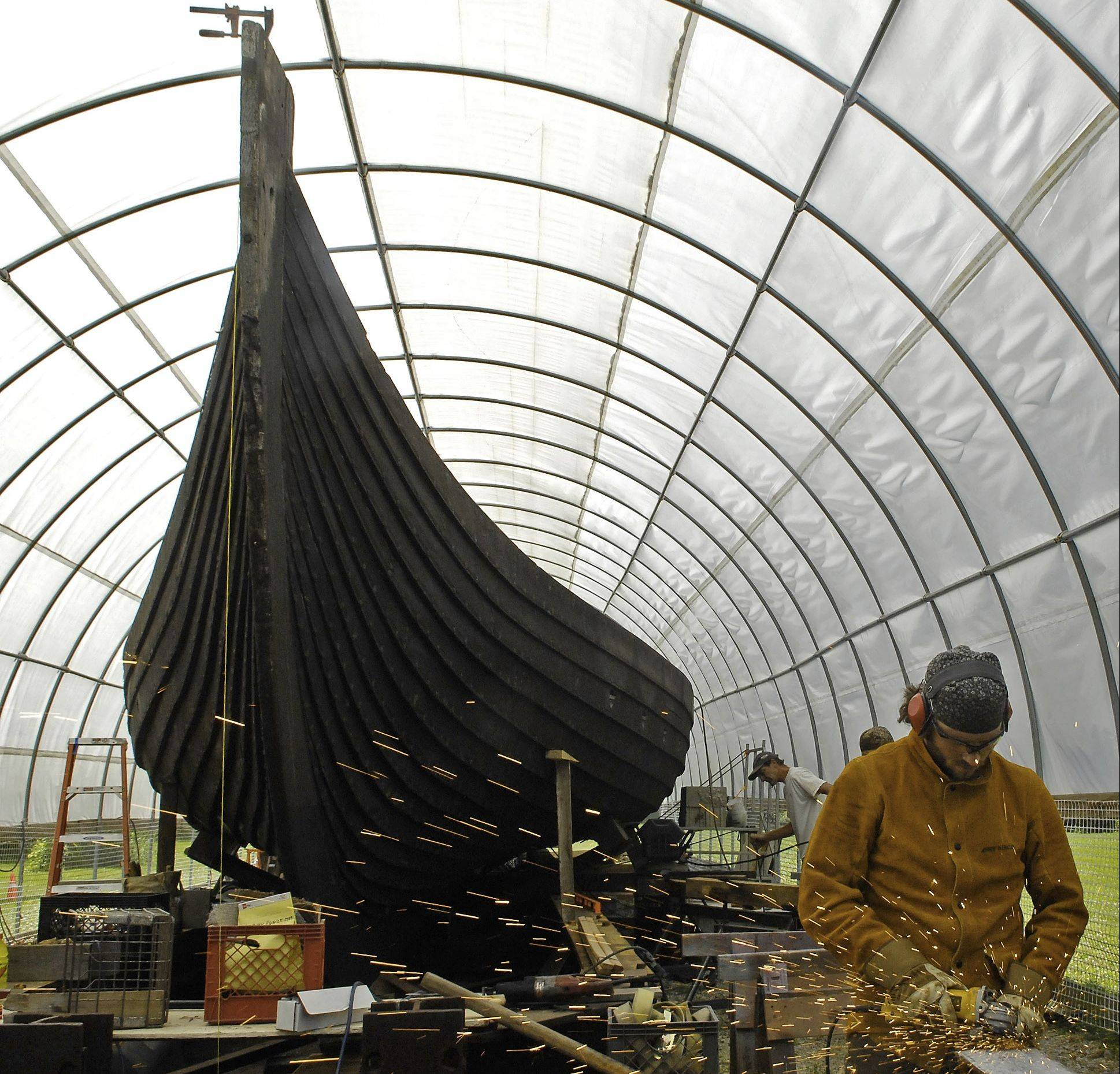 A worker grinds a piece of steel for a brace as work is done to stabilize and repair the replica Viking ship in Geneva. The copy of a 9th-century Viking ship was sailed to the Chicago from Norway for the World's Fair Columbian Exposition in 1893.