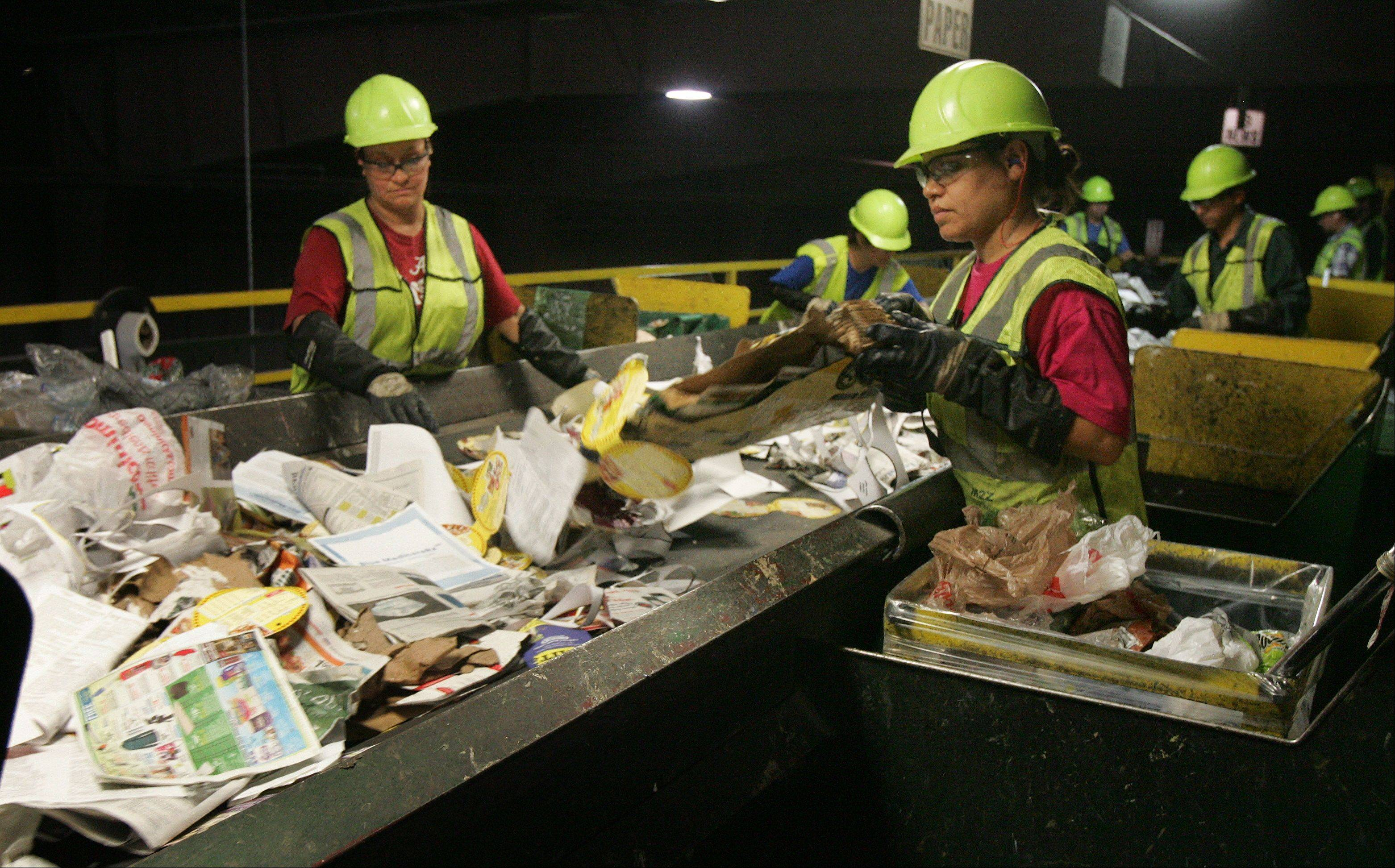 Workers at the Waste Management Recovery Facility in Grayslake separate materials to be recycled.