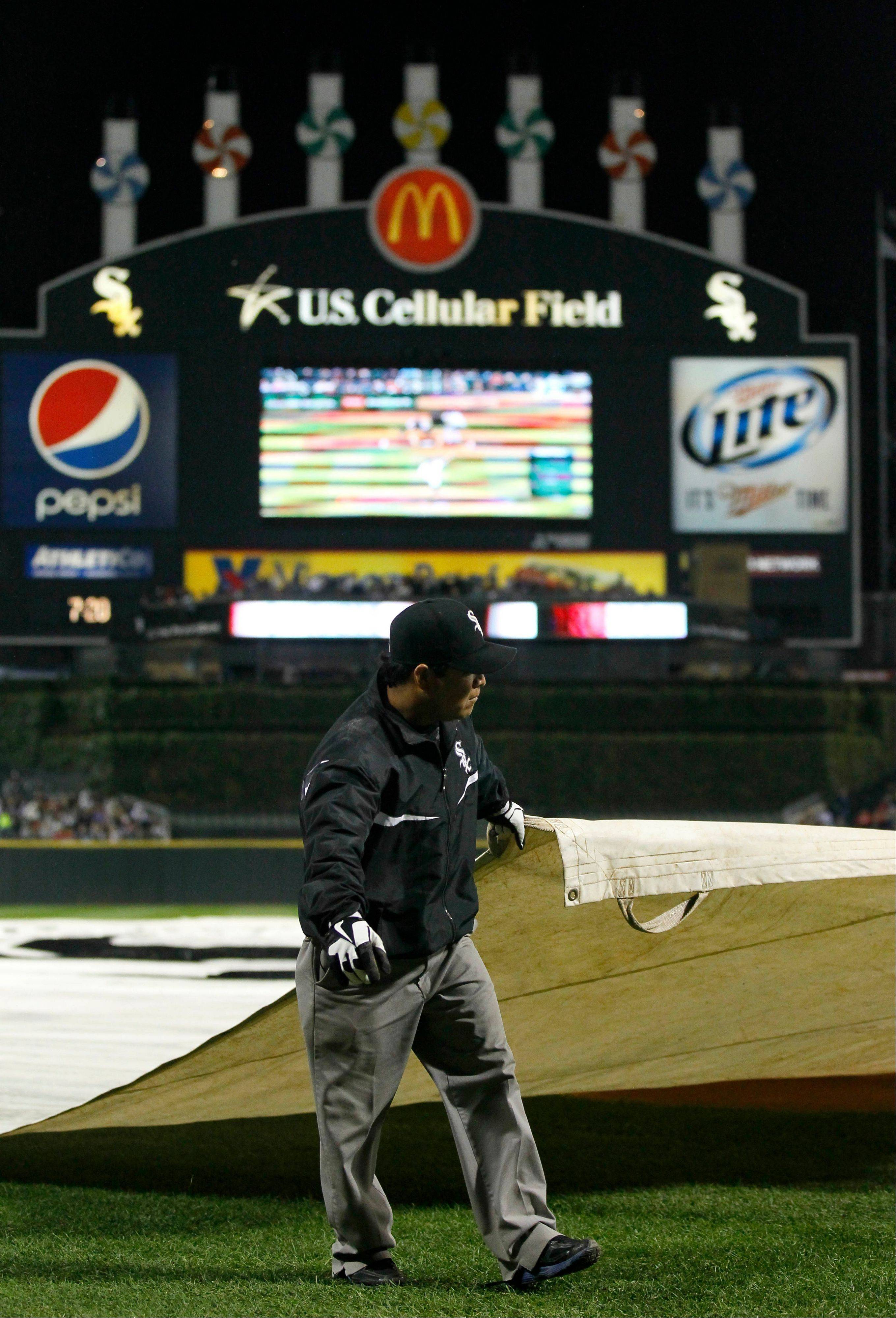 A member of the U.S. Cellular Field grounds crew helps cover the field as a rain delay postpones the start of Thursday's game the Detroit Tigers. The game eventually was rained out.