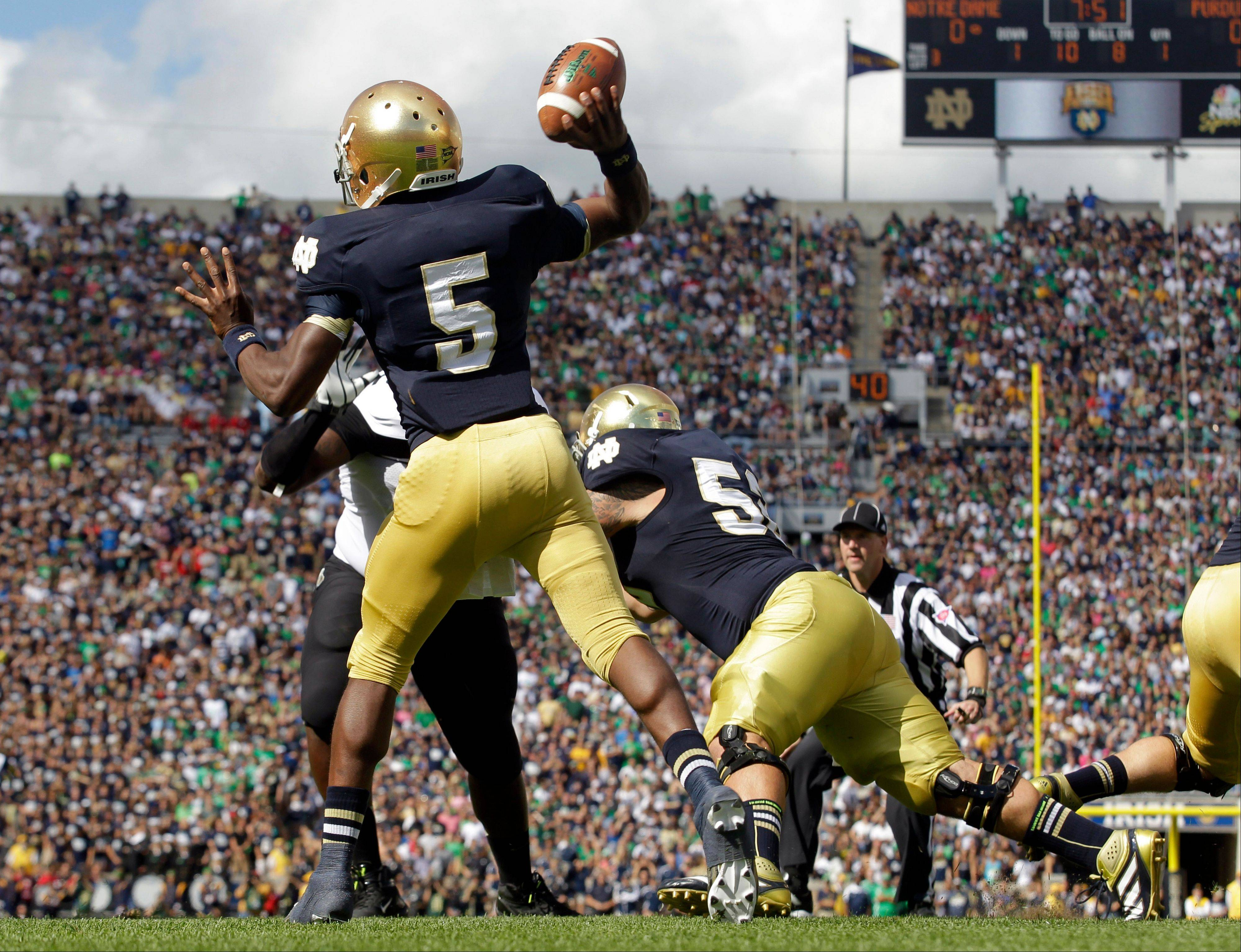 Notre Dame quarterback Everett Golson looks to pass as centner Braxston Cave, right, blocks during the first half against Purdue in South Bend, Ind. All too often last week the Irish offensive line struggled against Purdue, allowing four sacks and rushing for just 53 yards. The linemen are looking for redemption against No. 10 Michigan State's tough defensive line on Saturday.
