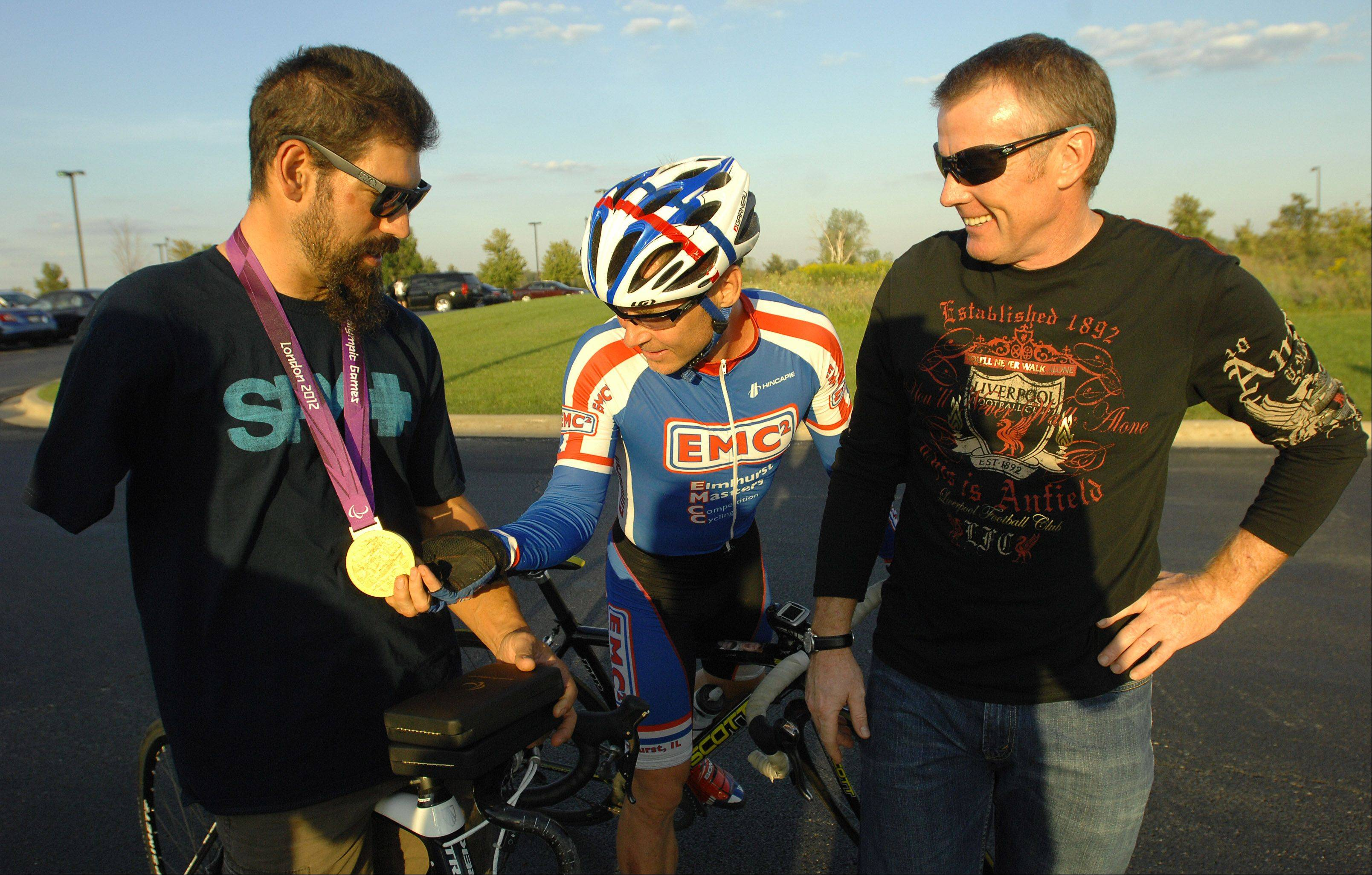 Aurora native and Paralympic gold, silver and bronze medalist Joe Berenyi, left, chats with Jostein Alvestad of Elmhurst and Andy Kerr of Batavia on Wednesday night before the start of practice races at a training session in West Chicago.