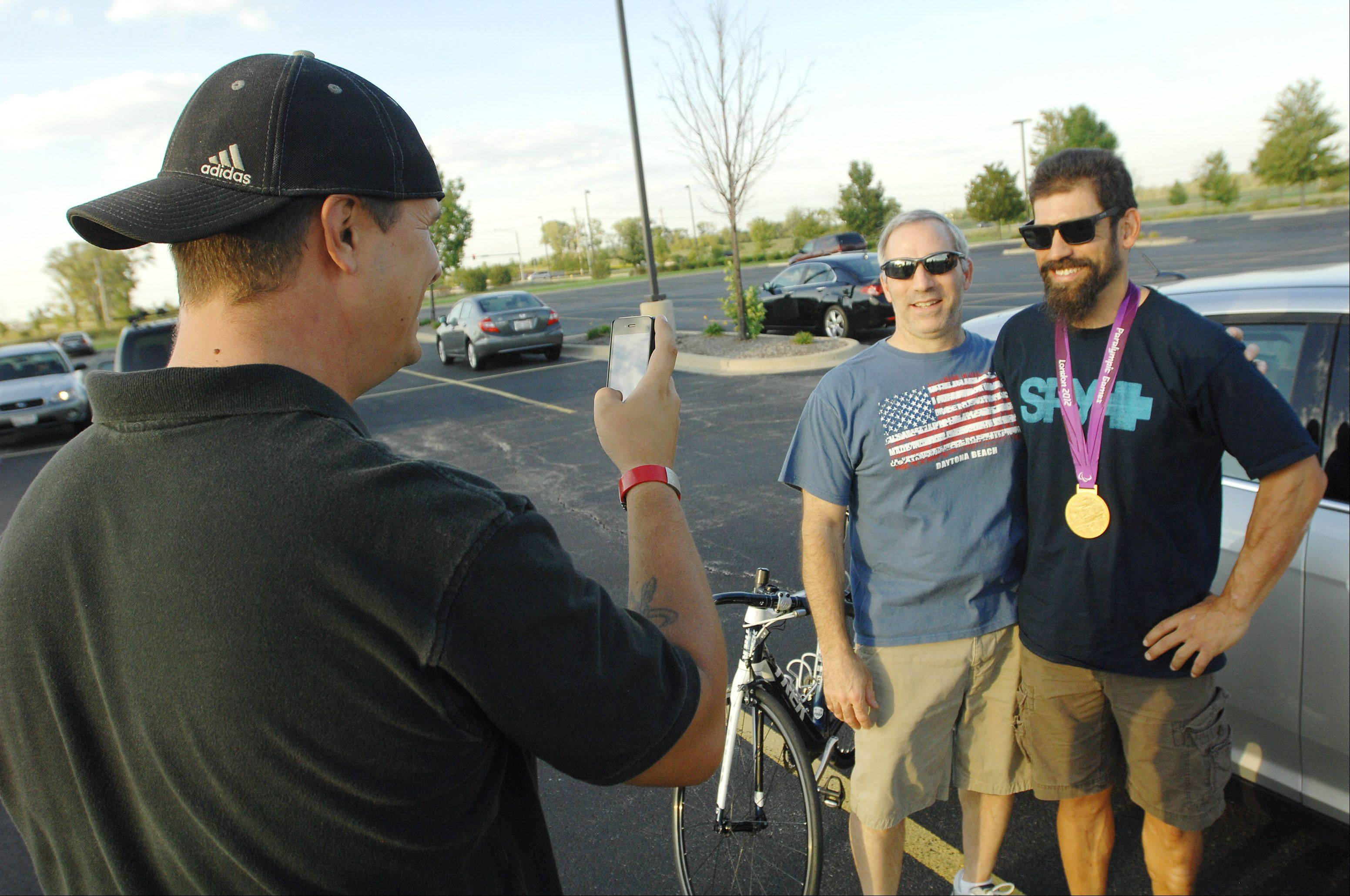 Aurora native and Paralympic gold, silver, and bronze medalist Joe Berenyi, right, poses for a photograph with Robert Riccio of North Aurora while hanging out on Wednesday night with other cyclists in West Chicago. Hanover Park resident Rich Johnson was taking the photo.