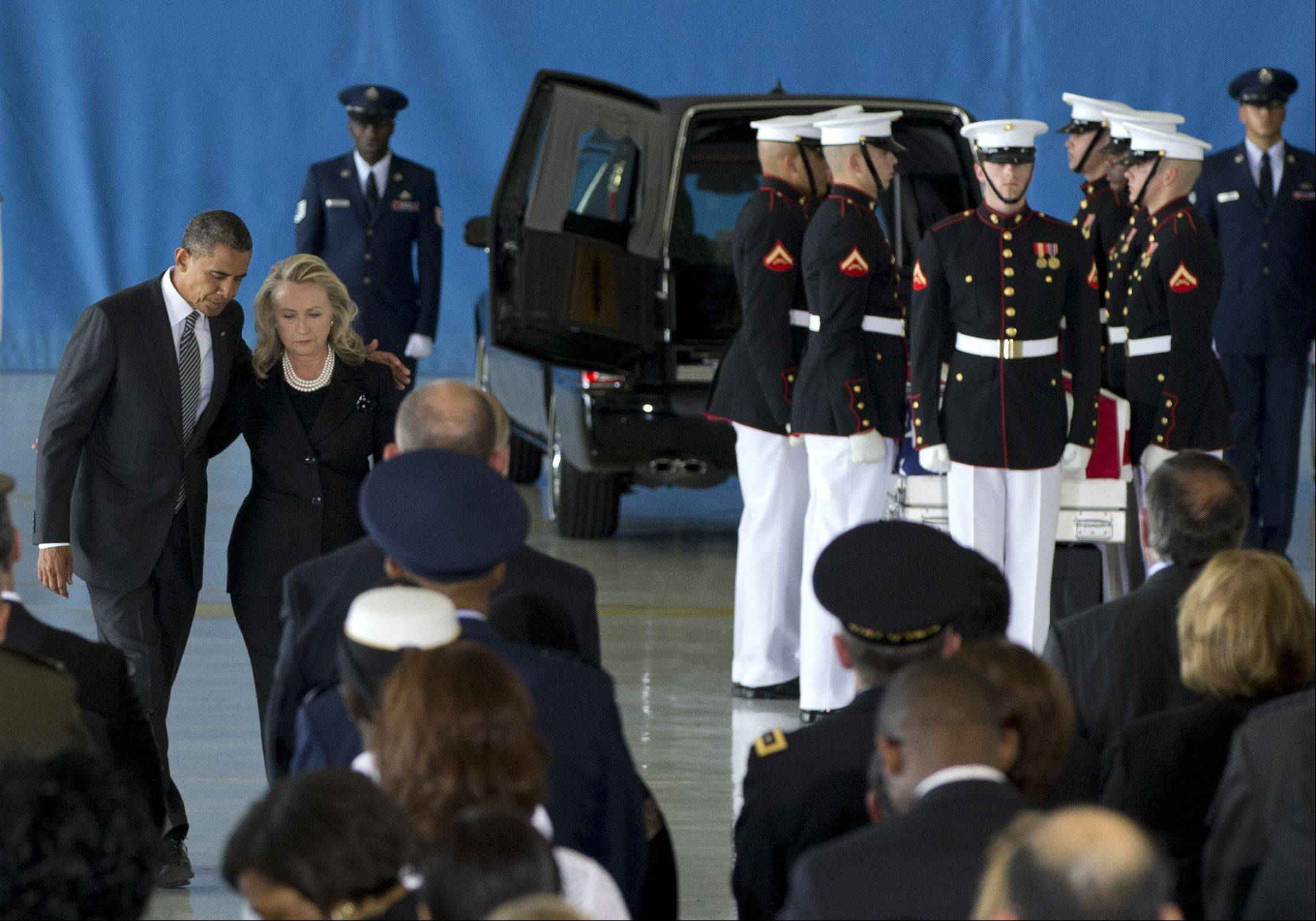 President Barack Obama and Secretary of State Hillary Rodham Clinton walk back to their seats Friday after speaking during the Transfer of Remains Ceremony at Andrews Air Force Base, Md.