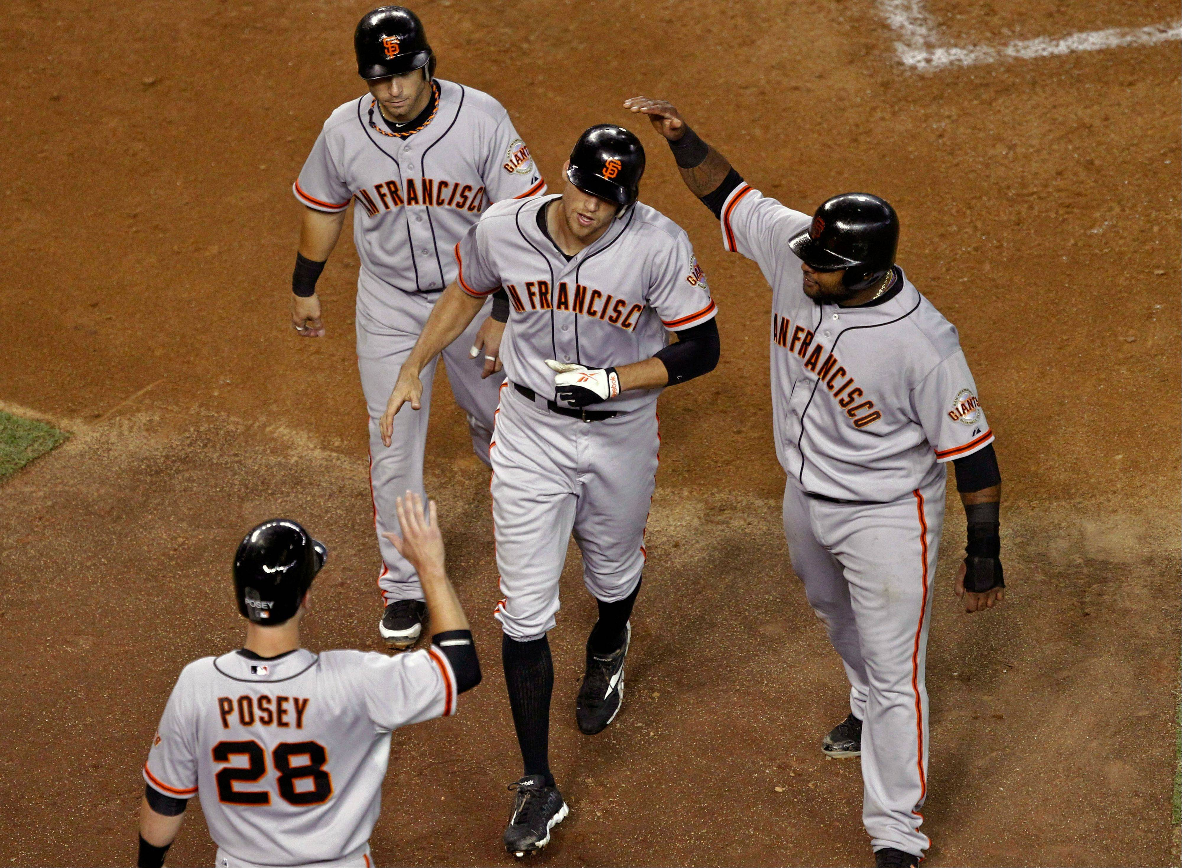 San Francisco's Buster Posey, Marco Scutaro, top left, and Pablo Sandoval, right, greet Hunter Pence after his a grand slam against the Arizona Diamondbacks during the third inning Friday in Phoenix.