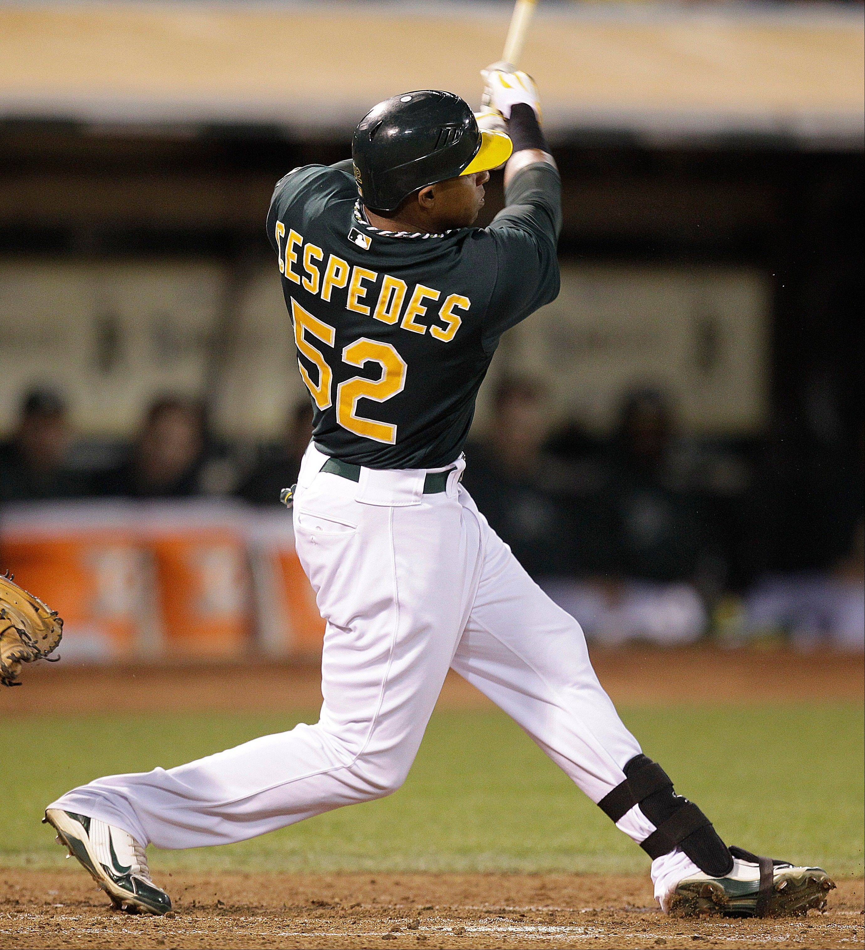 The Athletics' Yoenis Cespedes swings for a two-run home run off Baltimore's Joe Saunders in the fourth inning Friday in Oakland, Calif.
