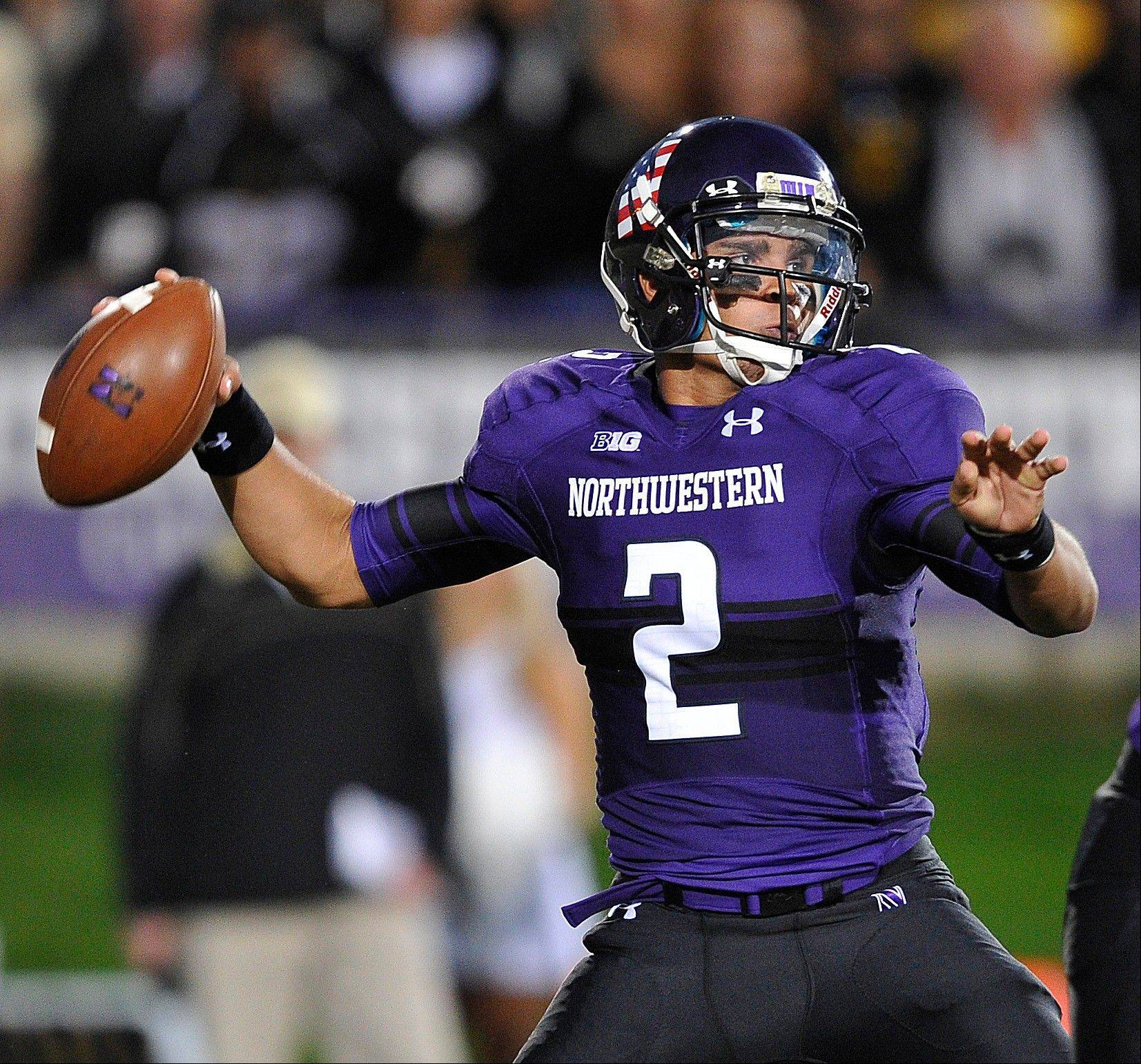 Kain Colter throws the ball downfield against Vanderbilt last Saturday. Colter is getting part of his pass protection this season from Montini grad Chuck Porcelli, a backup during his previous four years in Evanston.