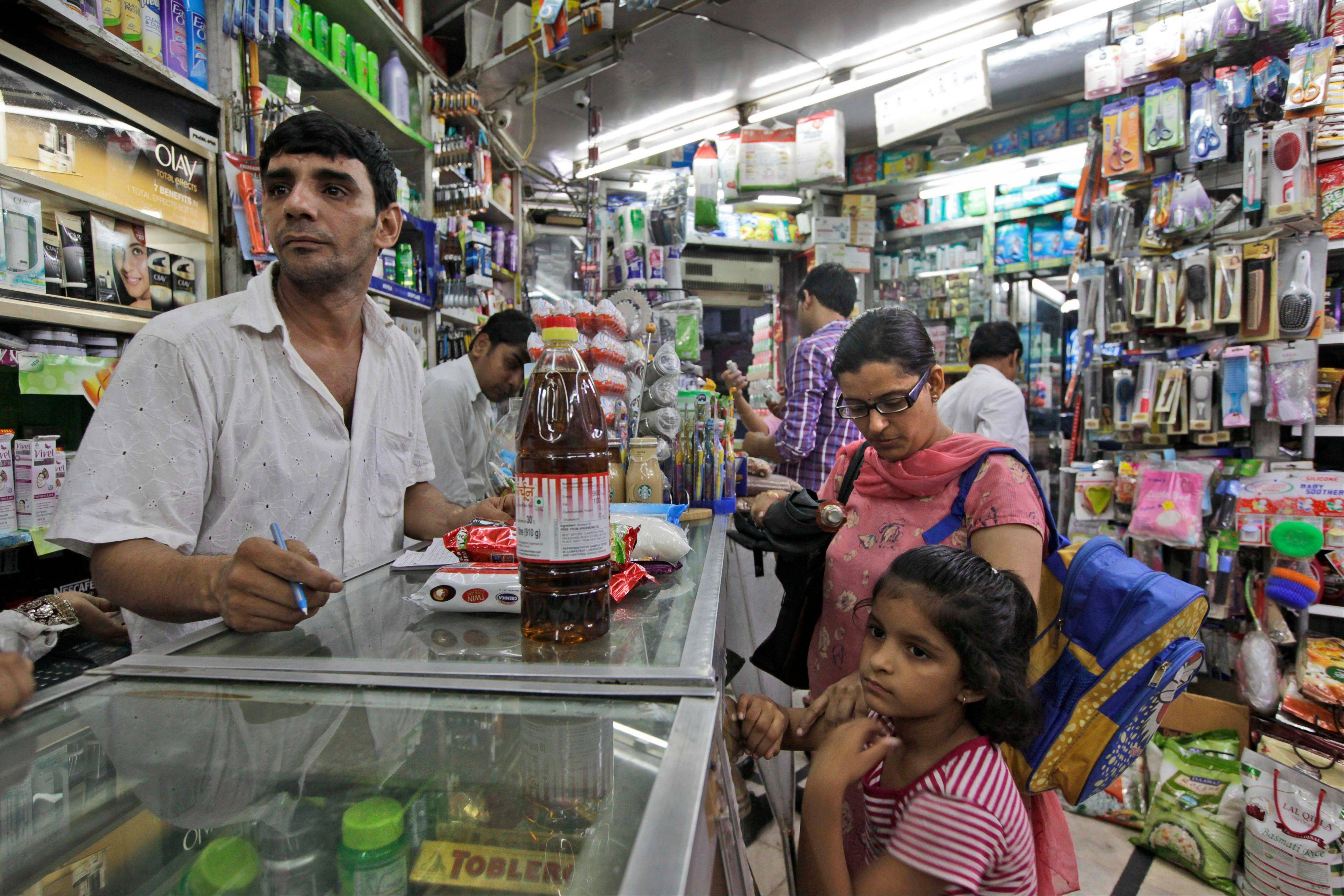 A young Indian girl with her mother waits for her order at a store, in New Delhi. India agreed Friday to open its huge market to foreign retailers such as Wal-Mart as part of a flurry of economic reforms aimed at sparking new growth in the country's sputtering economy.