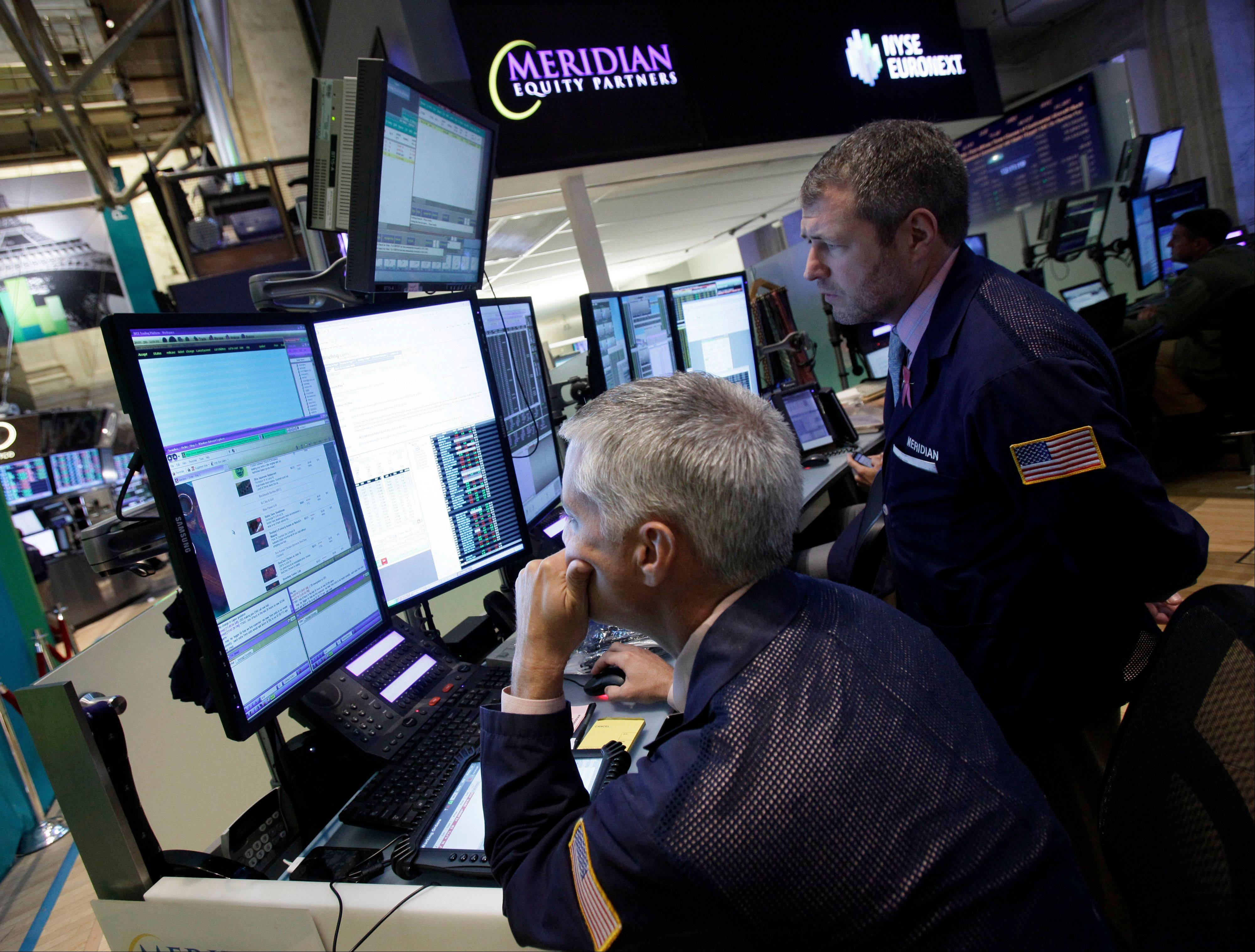A pair of traders work Thursday in their booth on the floor of the New York Stock Exchange.