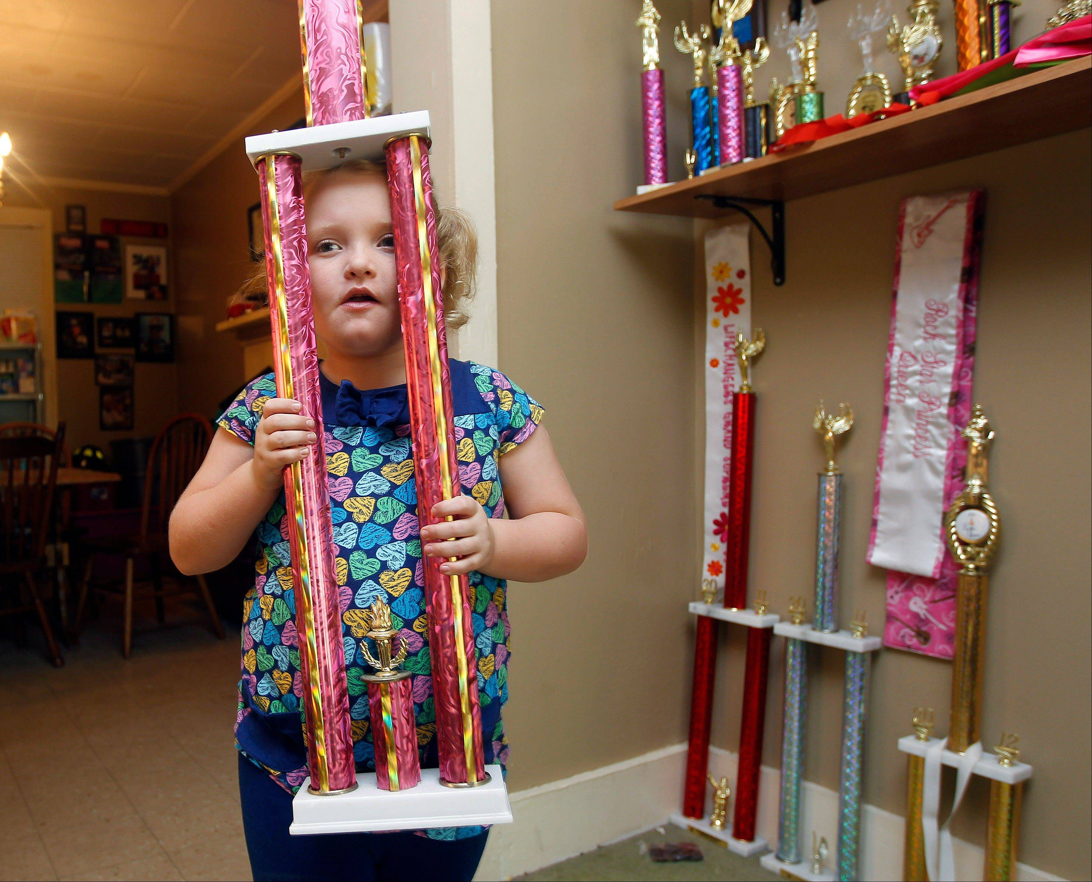 "Seven-year-old beauty pageant regular and reality show star Alana ""Honey Boo Boo"" Thompson shows one of her many trophies in her home in McIntyre, Ga. The reality show ""Here Comes Honey Boo Boo"" centers around Alana, her mother June Shannon and their family."