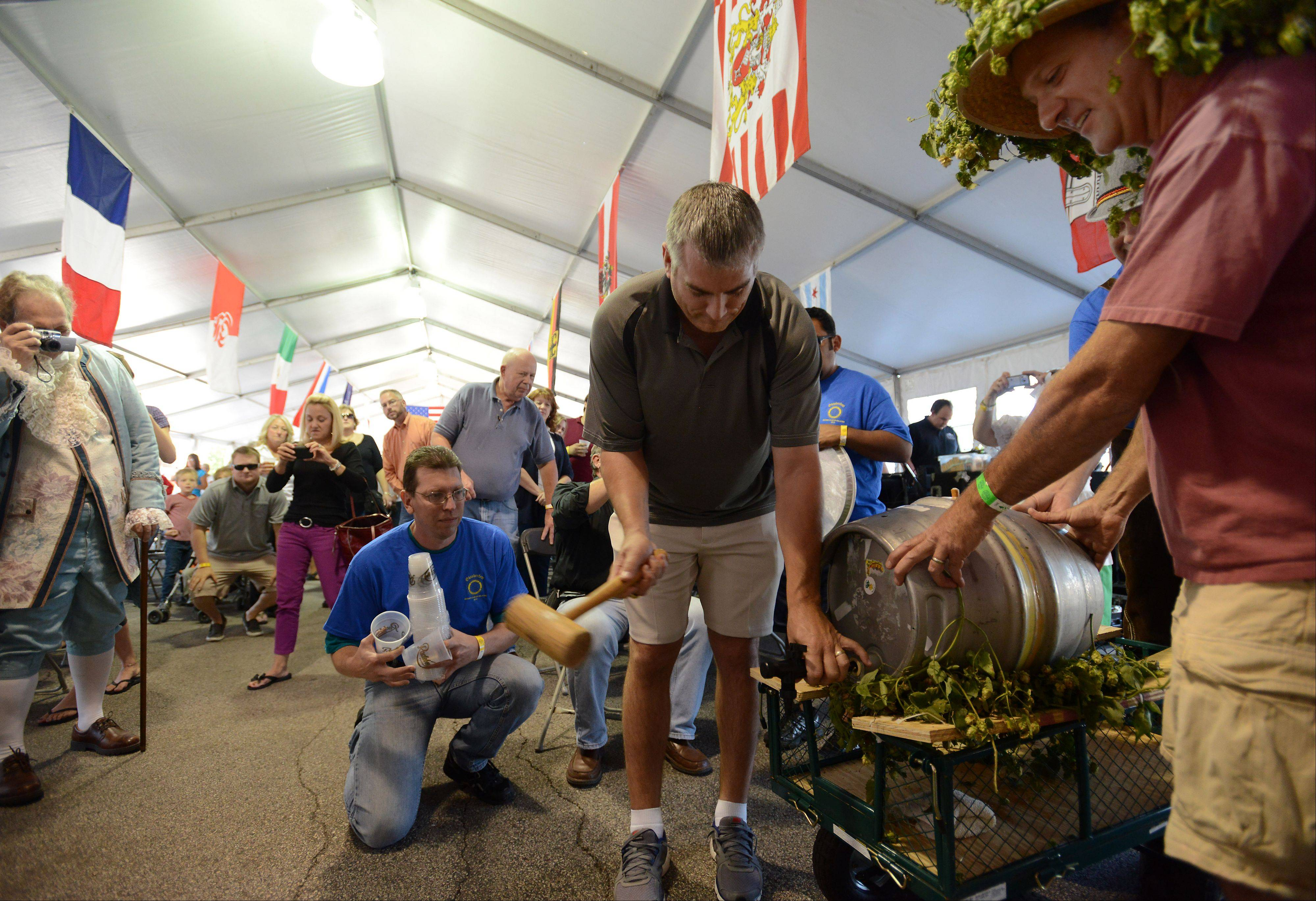 Palatine Mayor Jim Schwantz taps the firkin, a beer keg, to start off Oktoberfest in Palatine on Friday.