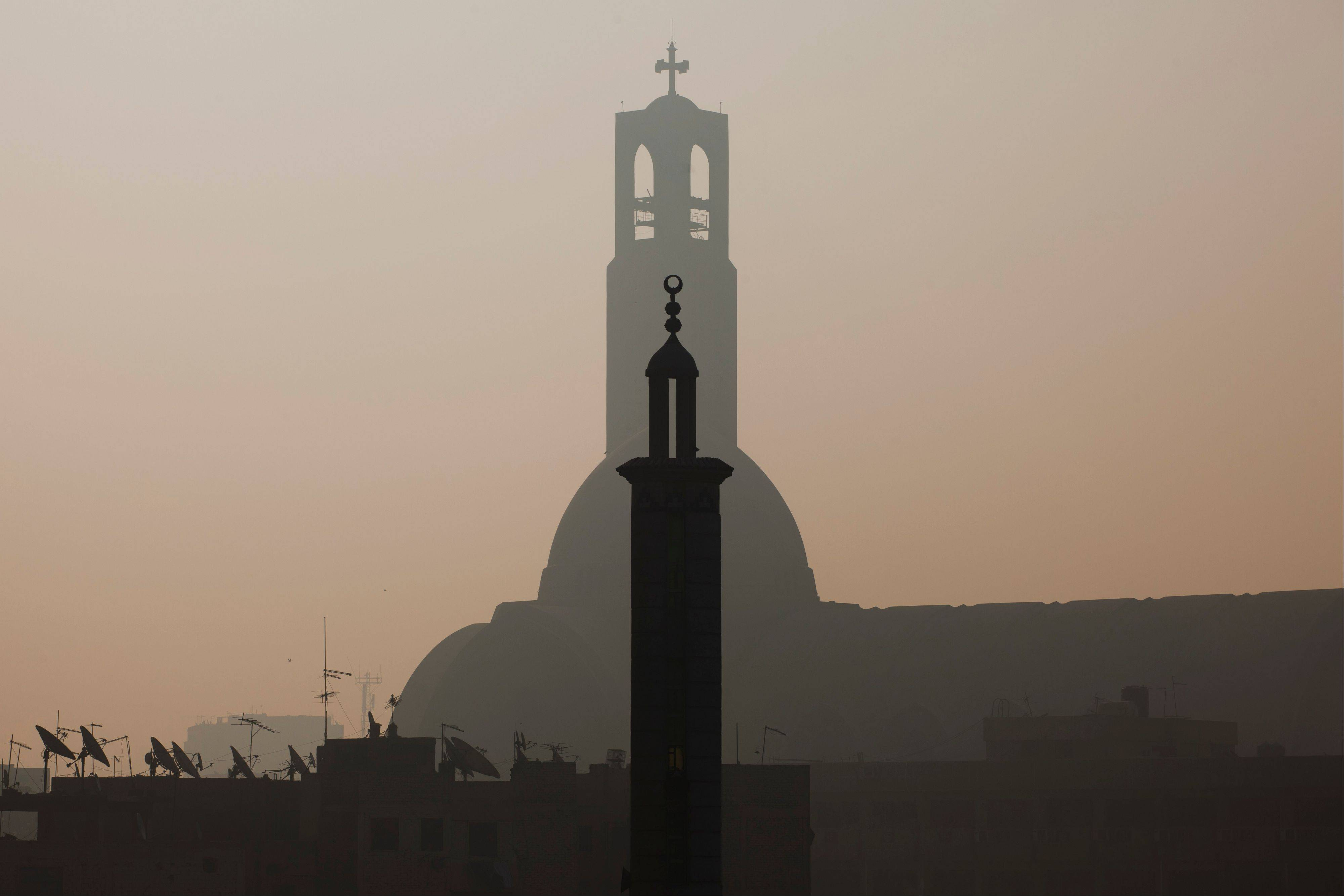 A minaret of a mosque is silhouetted in front of the St. Mark's Coptic Orthodox Cathedral in Cairo, Egypt.