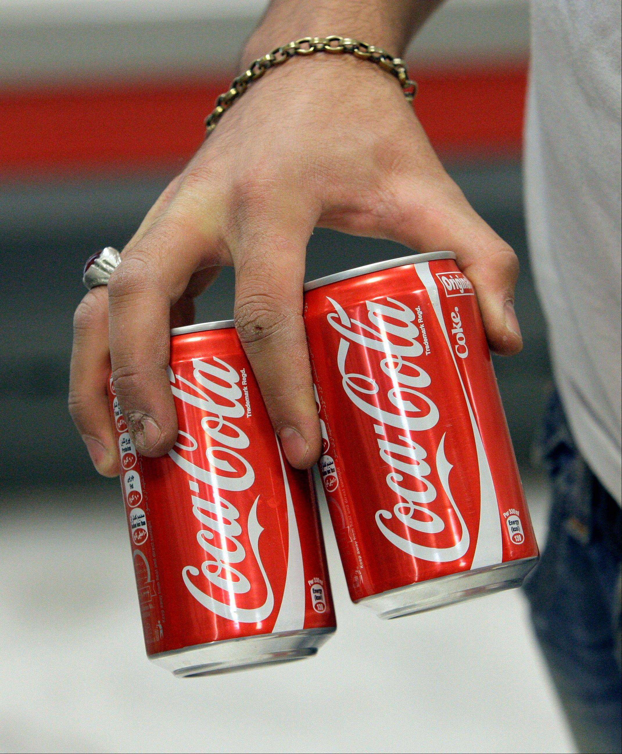 Associated Press/Sept. 8, 2012 Iranian worker Mahmoud Kouhi, carries cans of Coke, in a grocery store in northern Tehran.