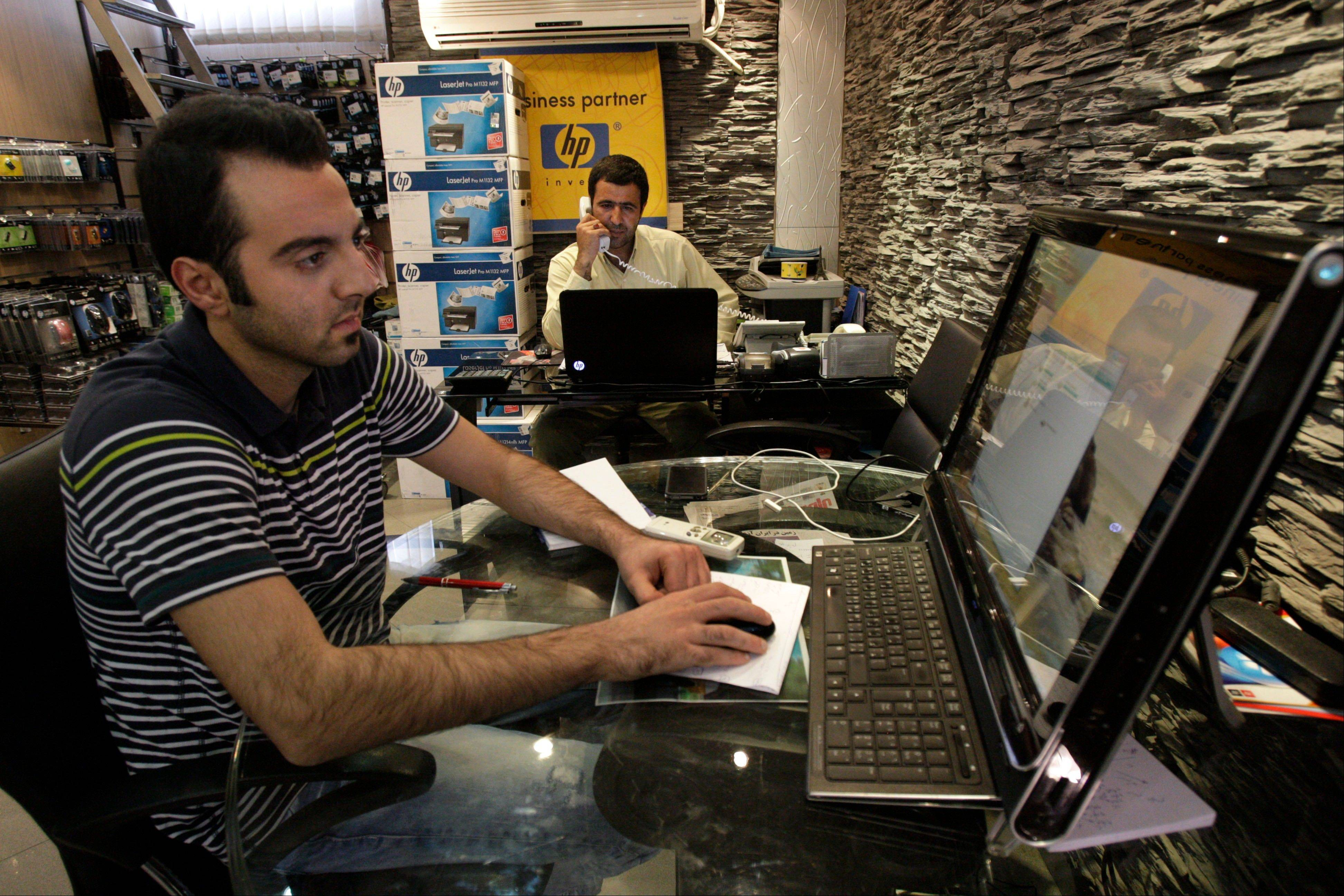 Associated Press/Sept. 8, 2012Iranian shopkeeper Mohammad Mousavi, background, a Hewlett-Packard, HP, products seller, speaks on the phone, as Vedad Rashadi, works on a computer, in their store, in an electronics market in northern Tehran, Iran.