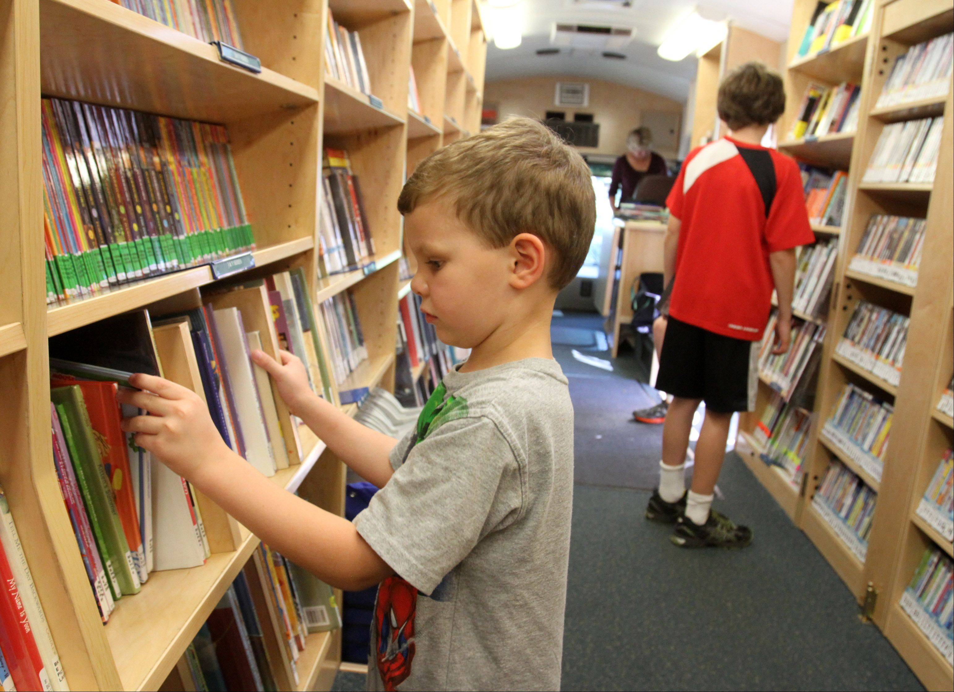 Four-year-old Jake Bozikis of Arlington Heights looks at children's books while visiting the Arlington Heights Memorial Library bookmobile with his mom, Michele, on Sept. 12, near Olive-Mary Stitt Elementary School.