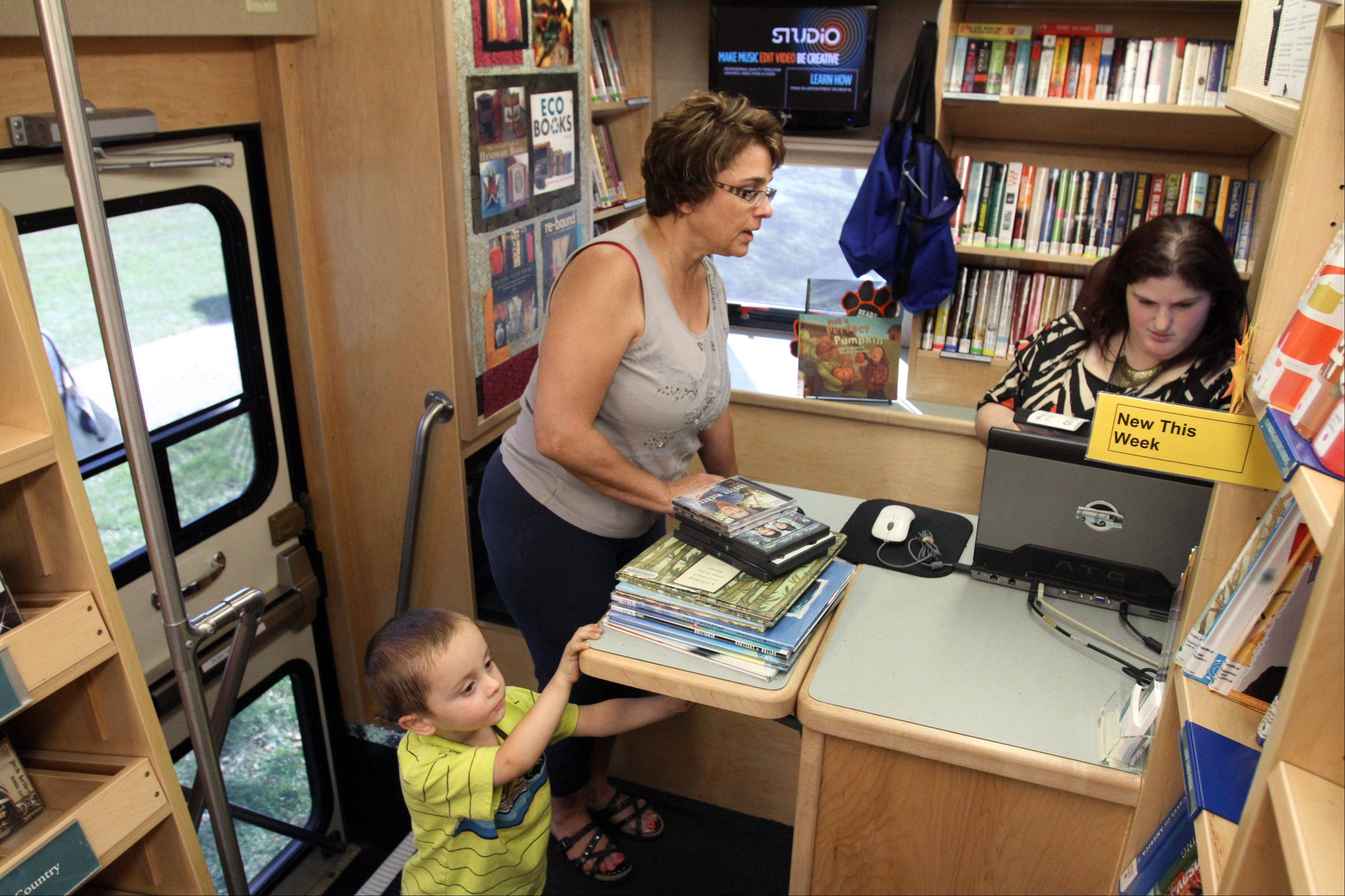 Liz Wojtkowski and her grandson, Tyler, 3, check out a stack of children's books from bookmobile assistant Amy Henkels in the Arlington Heights Memorial Library bookmobile parked near Olive-Mary Stitt Elementary School on Sept. 12.