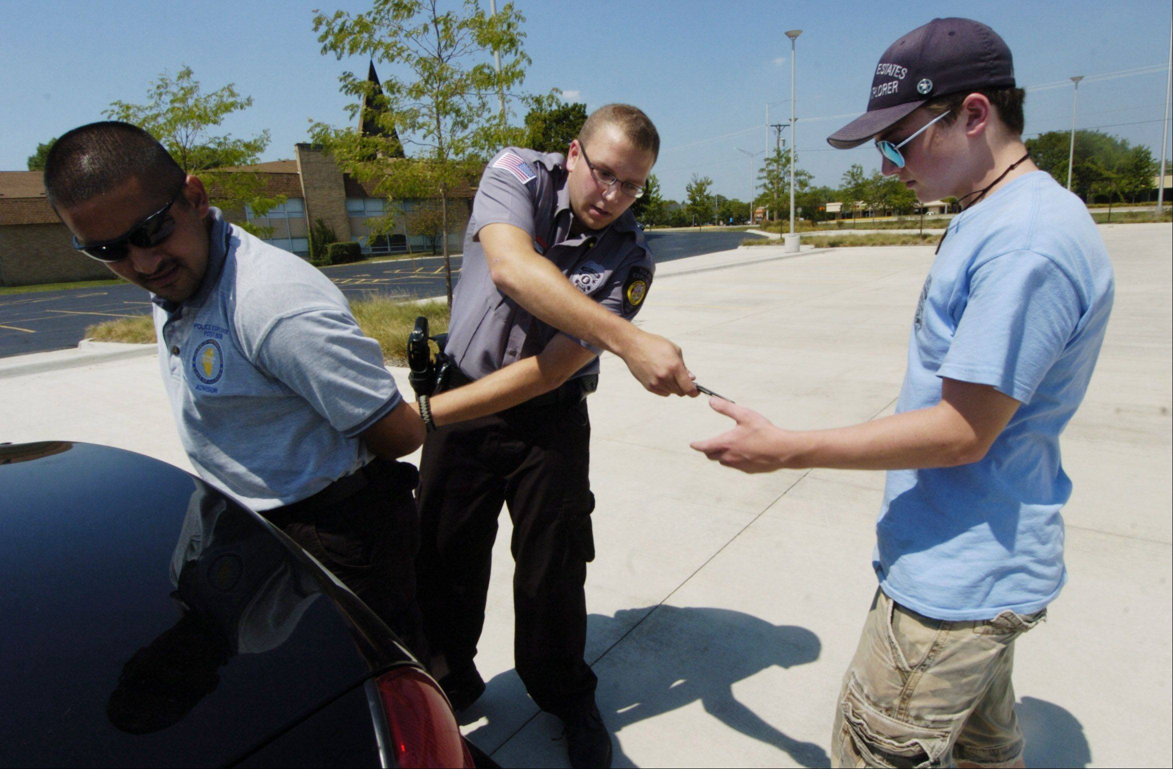 "Hoffman Estates Police Explorer Phil Giacone hands items from the pockets of ""suspect"" Farhad Mujahed, to the post's adviser -- and backup officer -- Joe Notarnicola during a simulated felony traffic stop."