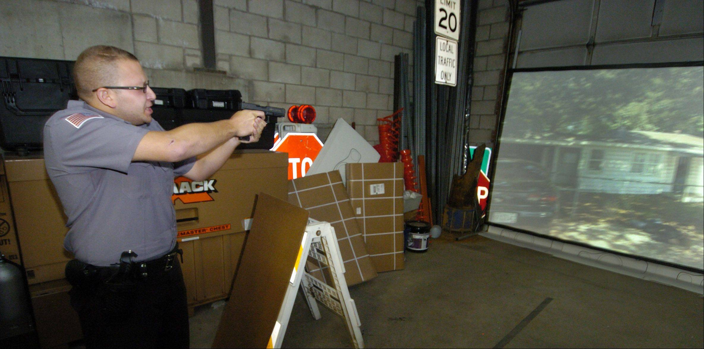 Hoffman Estates Police Explorer Phil Giacone aims his weapon while undergoing training with the Meggitt XVT firearms simulator at the South Barrington police station.