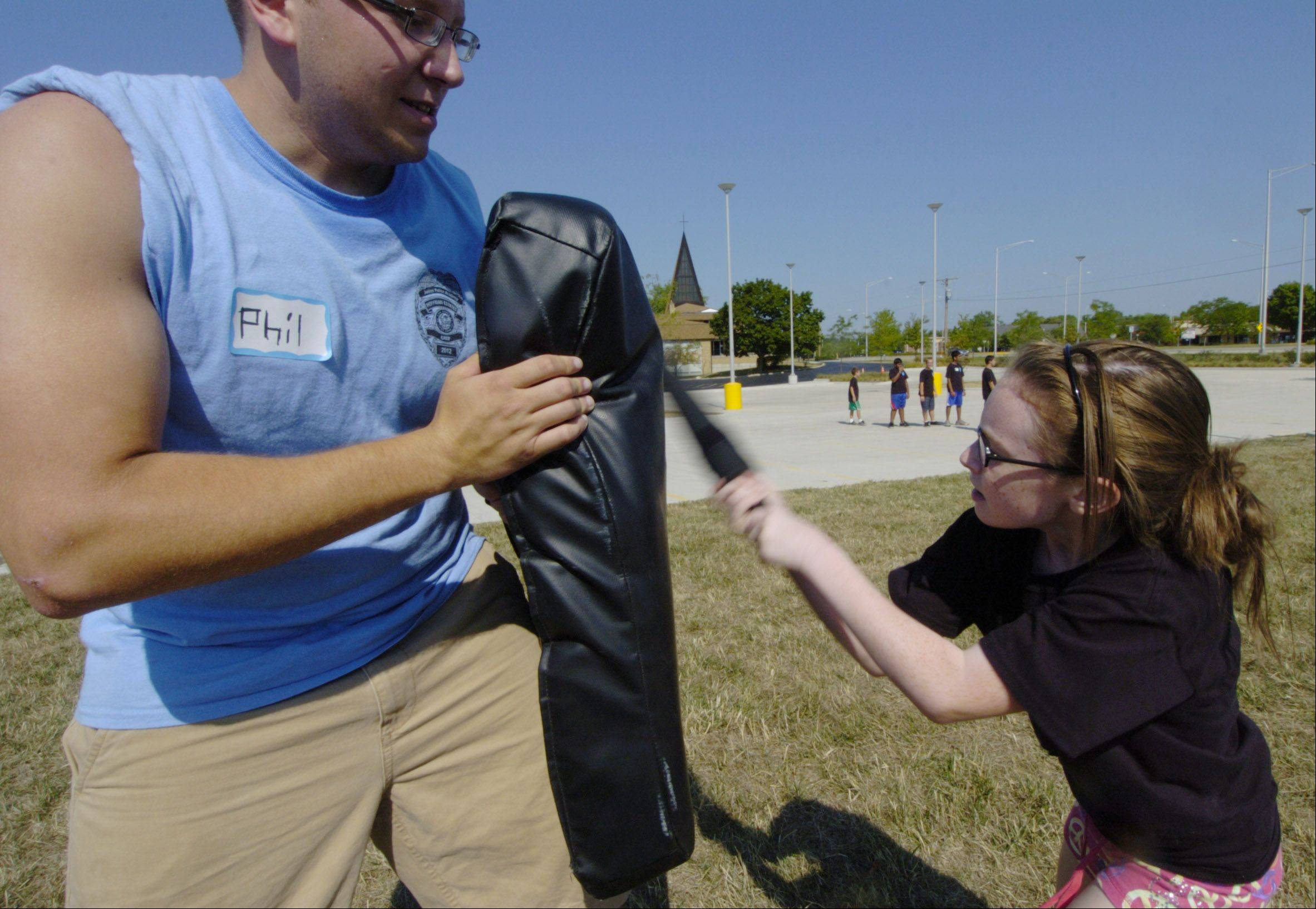 Though he's more than three times her size, Hoffman Estates Police Explorer Phil Giacone holds on tightly to the blocking dummy as Mikala Janicki, 11, of Hoffman Estates strikes a blow with a flexible training baton during an obstacle course on the final day of the Junior Police Academy.