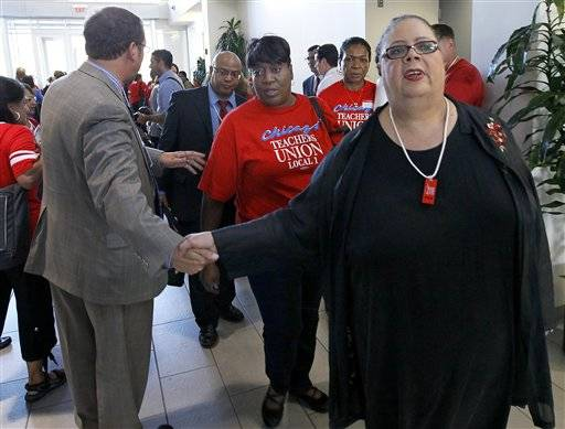 "Karen Lewis, president of the Chicago teachers union, departs a news conference after her meeting with the union's House of Delegates Sept. 14 in Chicago. Lewis told the delegates that a ""framework"" was in place to end the teachers strike."