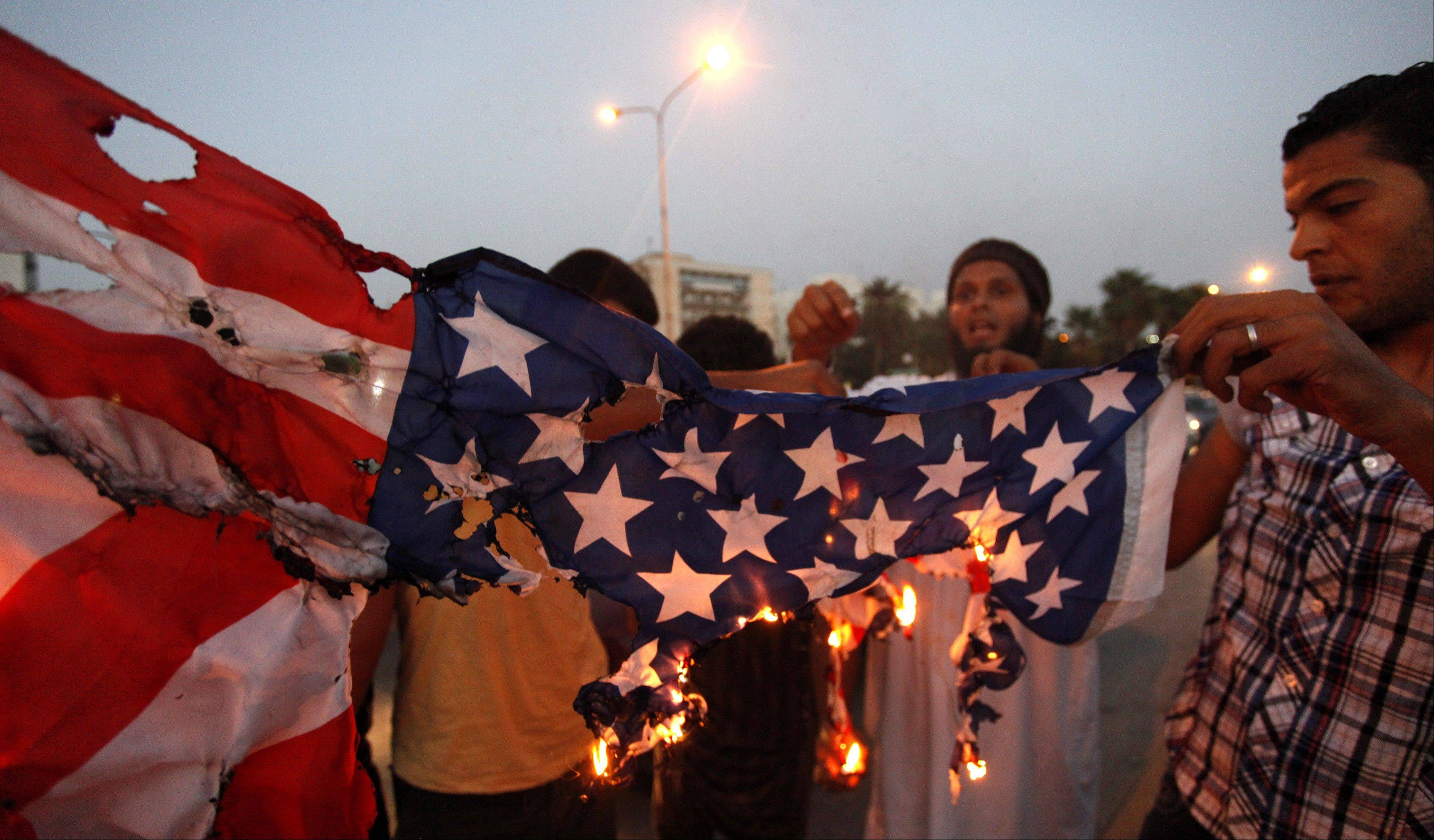 Libyan followers of Ansar al-Shariah Brigades burn the U.S. flag Friday during a protest in front of the Tibesti Hotel, in Benghazi, Libya.