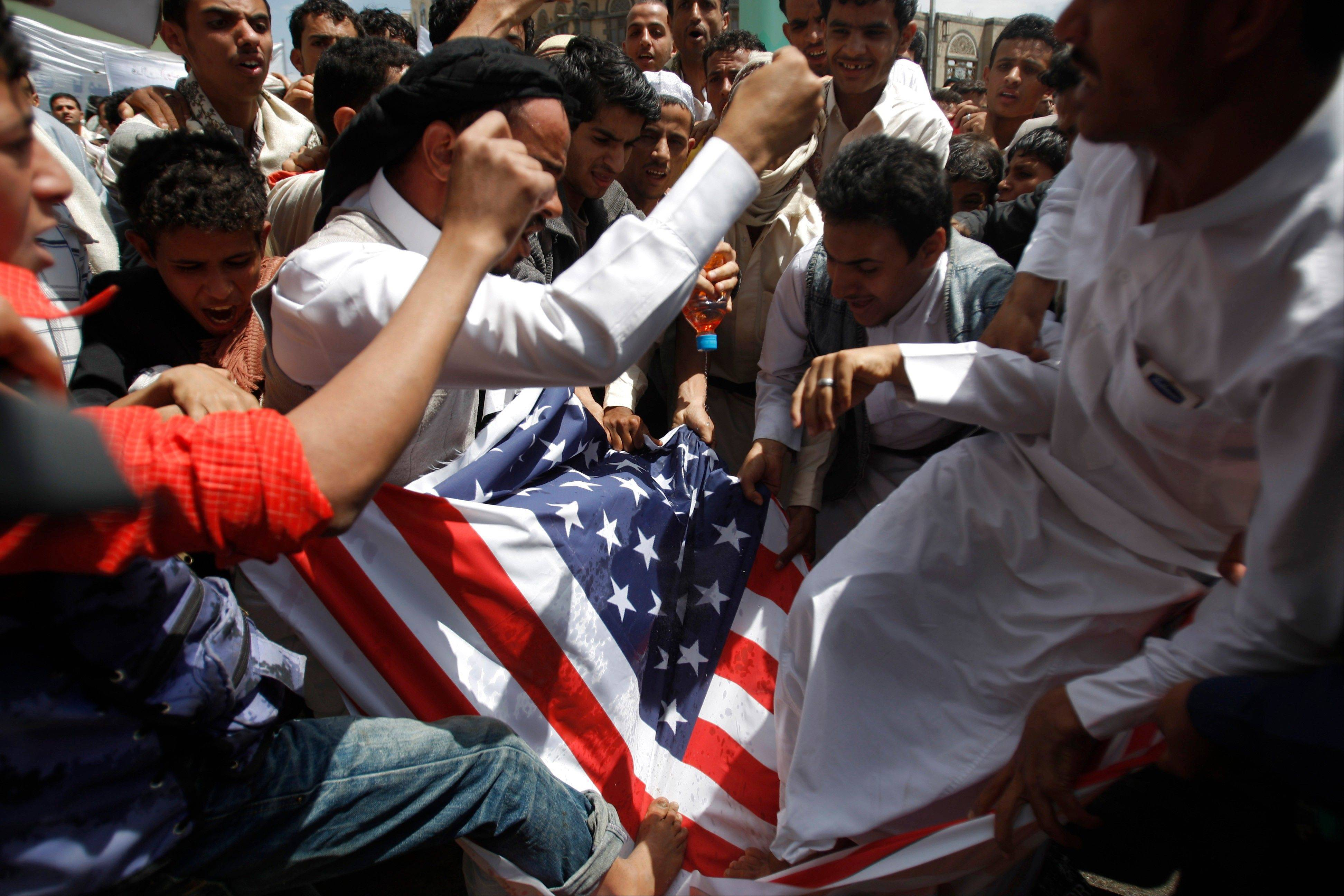 Protesters destroy an American flag pulled down during clashes with police near the U.S. Embassy in Sanaa, Yemen, Friday, Sept. 14, 2012, as part of widespread anger across the Muslim world about a film ridiculing Islam's Prophet Muhammad.