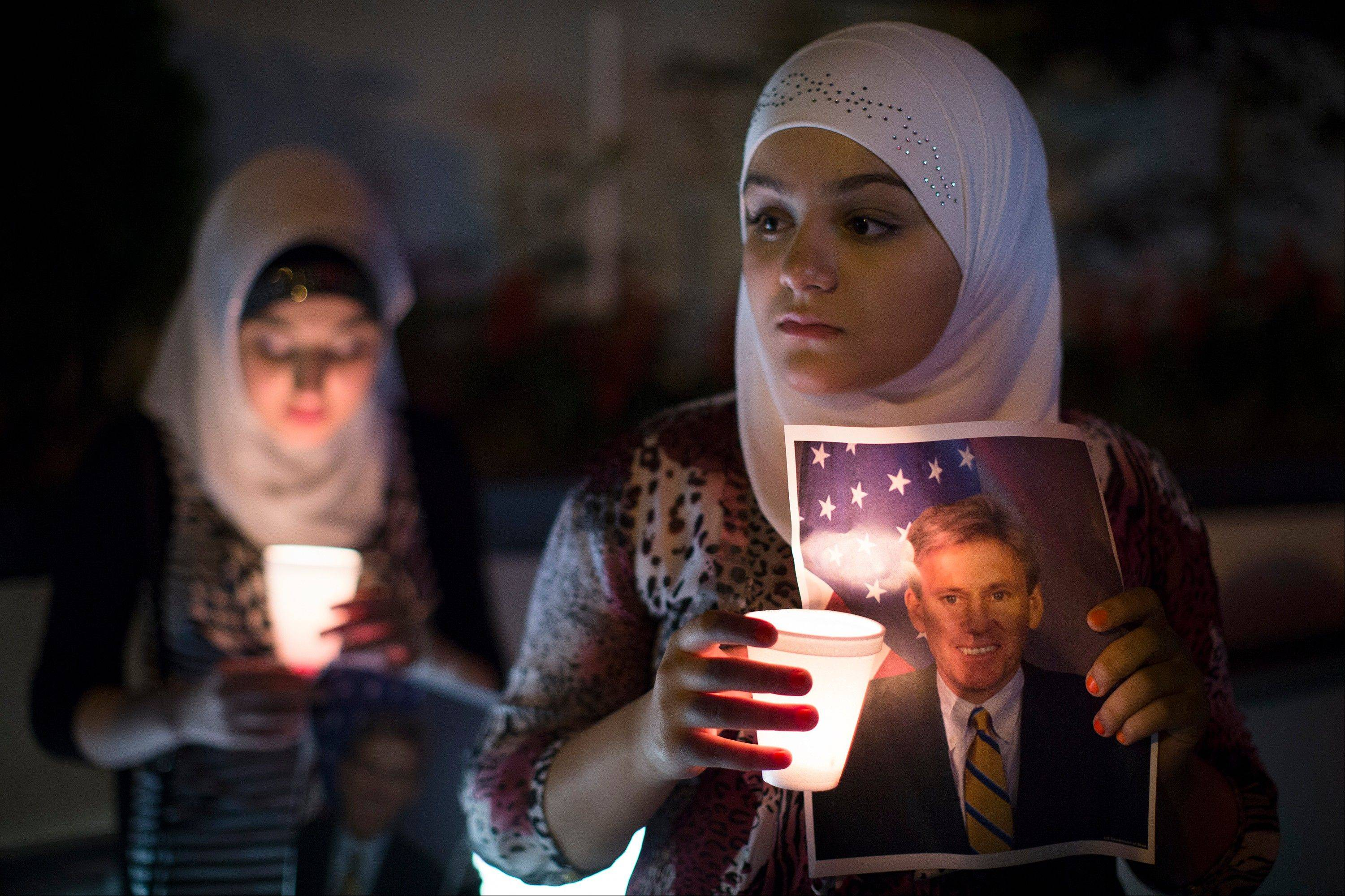 Dilan Samo, 13, holds a picture of slain U.S. ambassador to Libya Christopher Stevens during a candlelight vigil outside the Libyan Embassy, Thursday, Sept. 13, 2012, in New York. Stevens was killed by an angry mob during an assault on the American embassy in Benghazi that stemmed from the widespread anger generated by an American made anti-Muslim film.