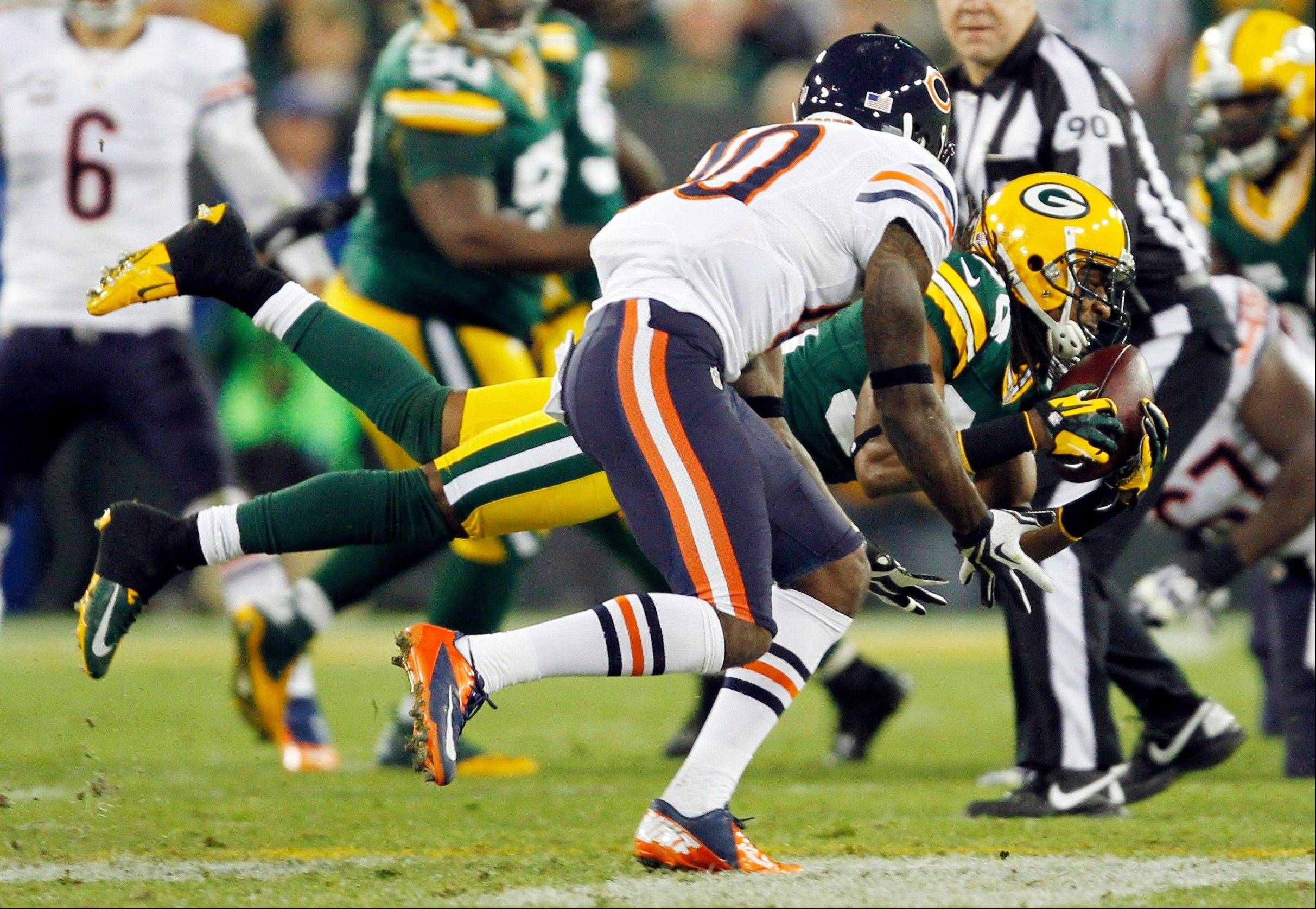 Green Bay Packers' Tramon Williams intercepts a pass in front of Chicago Bears' Earl Bennett during the first half.