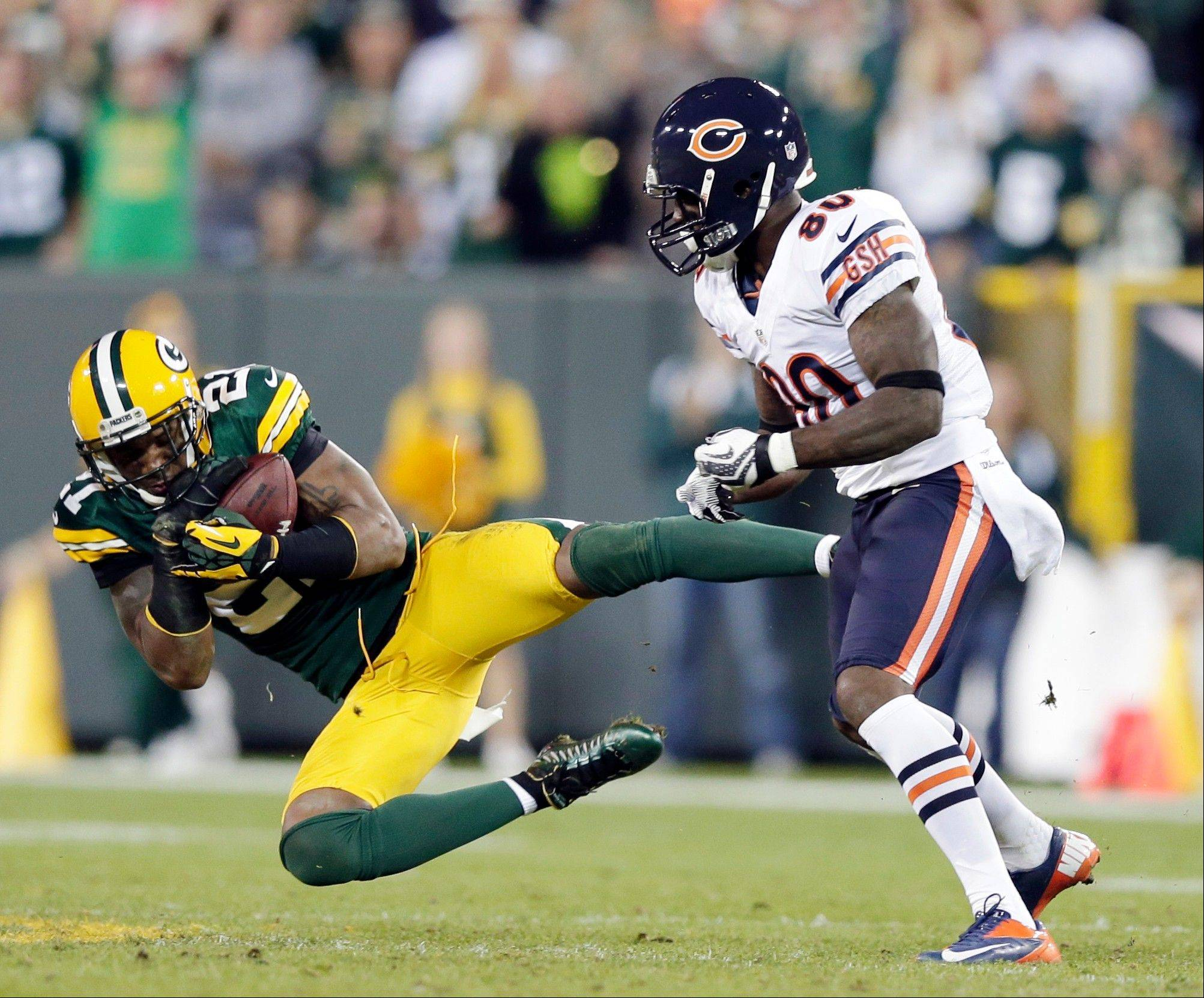 Green Bay Packers' Charles Woodson intercepts a pass in front of Chicago Bears' Earl Bennett during the second half .
