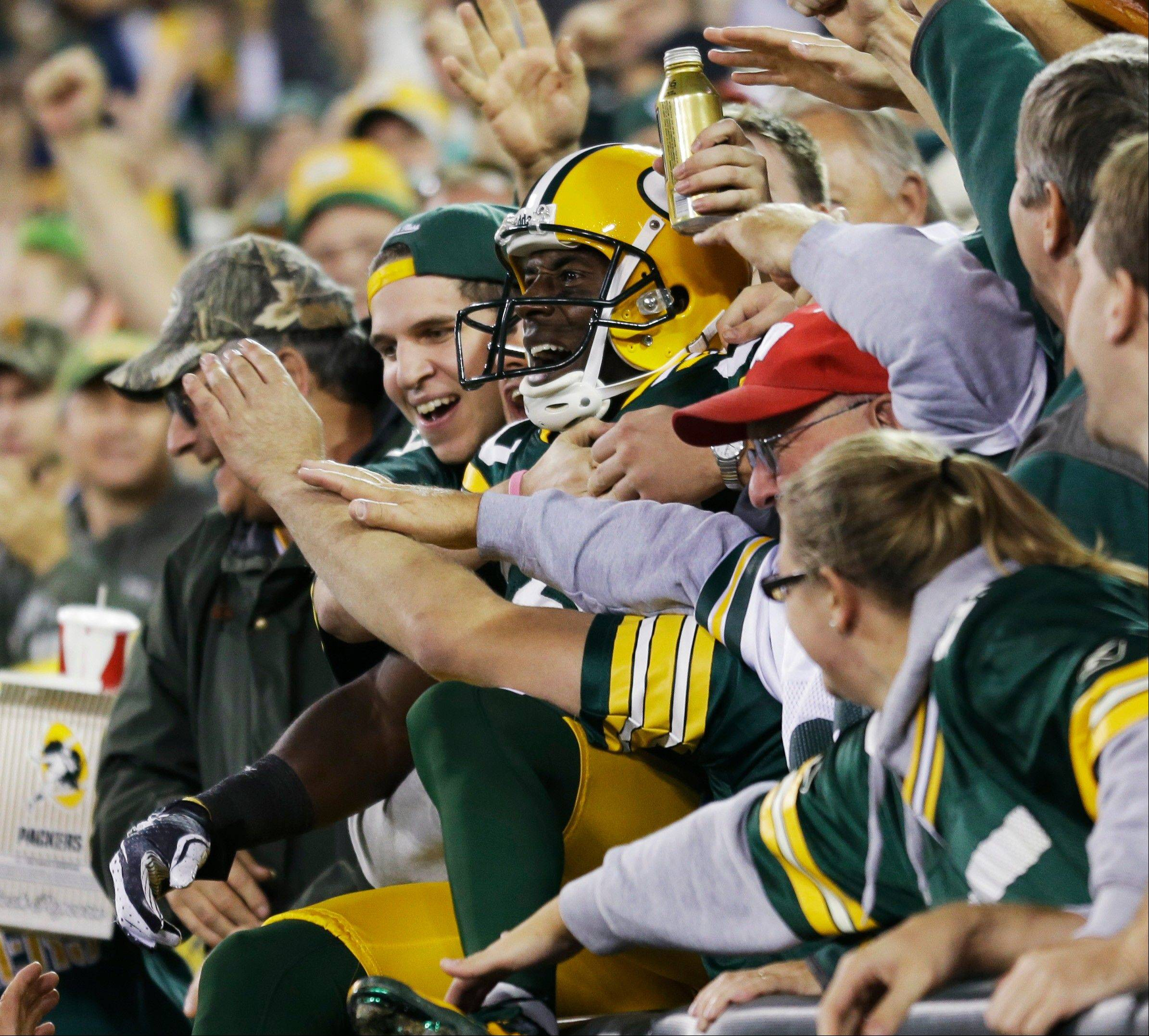 Green Bay Packers' Donald Driver celebrates with fans after catching a touchdown pass during the second half.