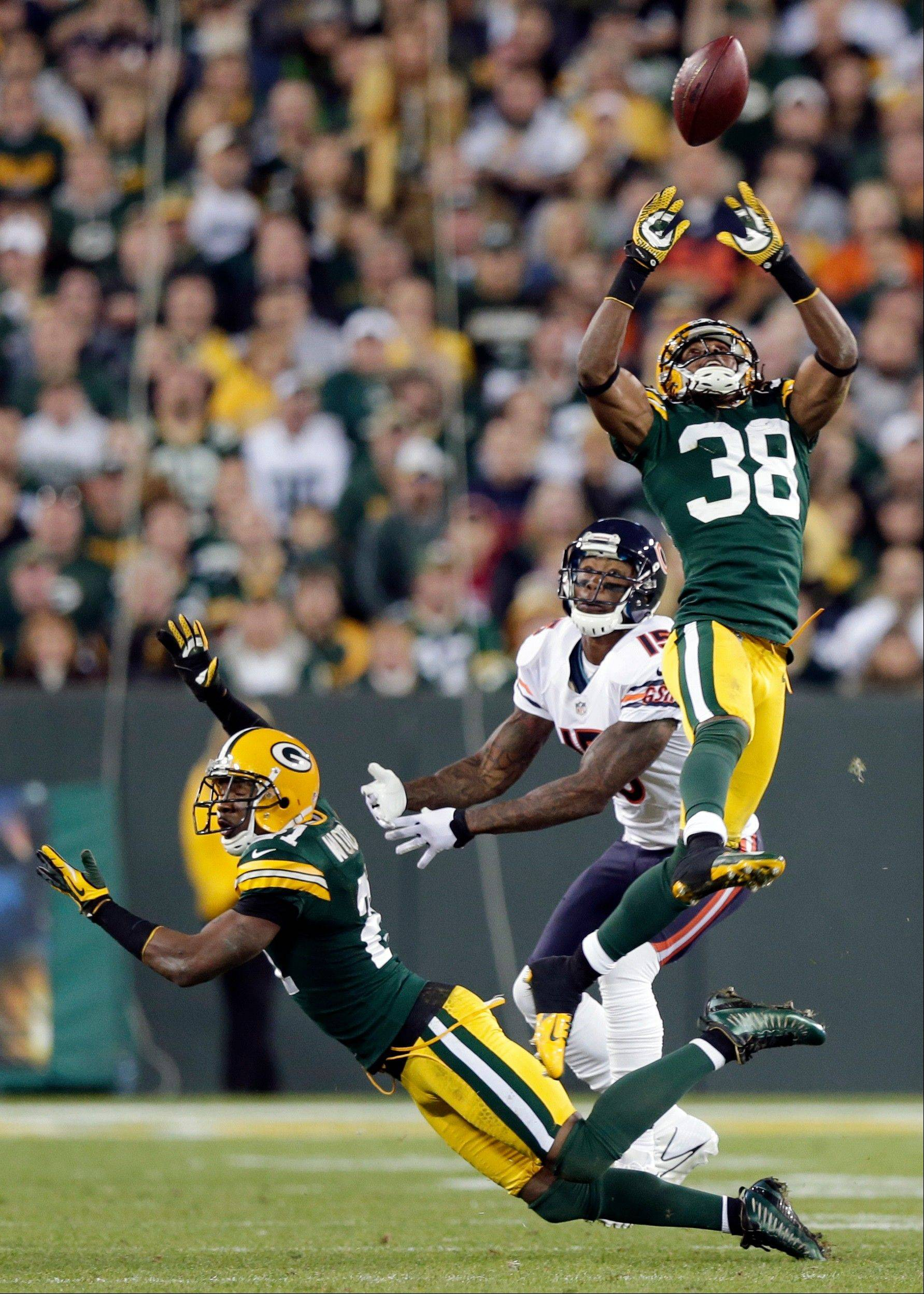 Green Bay Packers' Tramon Williams intercepts a pass in front of Chicago Bears' Brandon Marshall and Charles Woodson during the second half.
