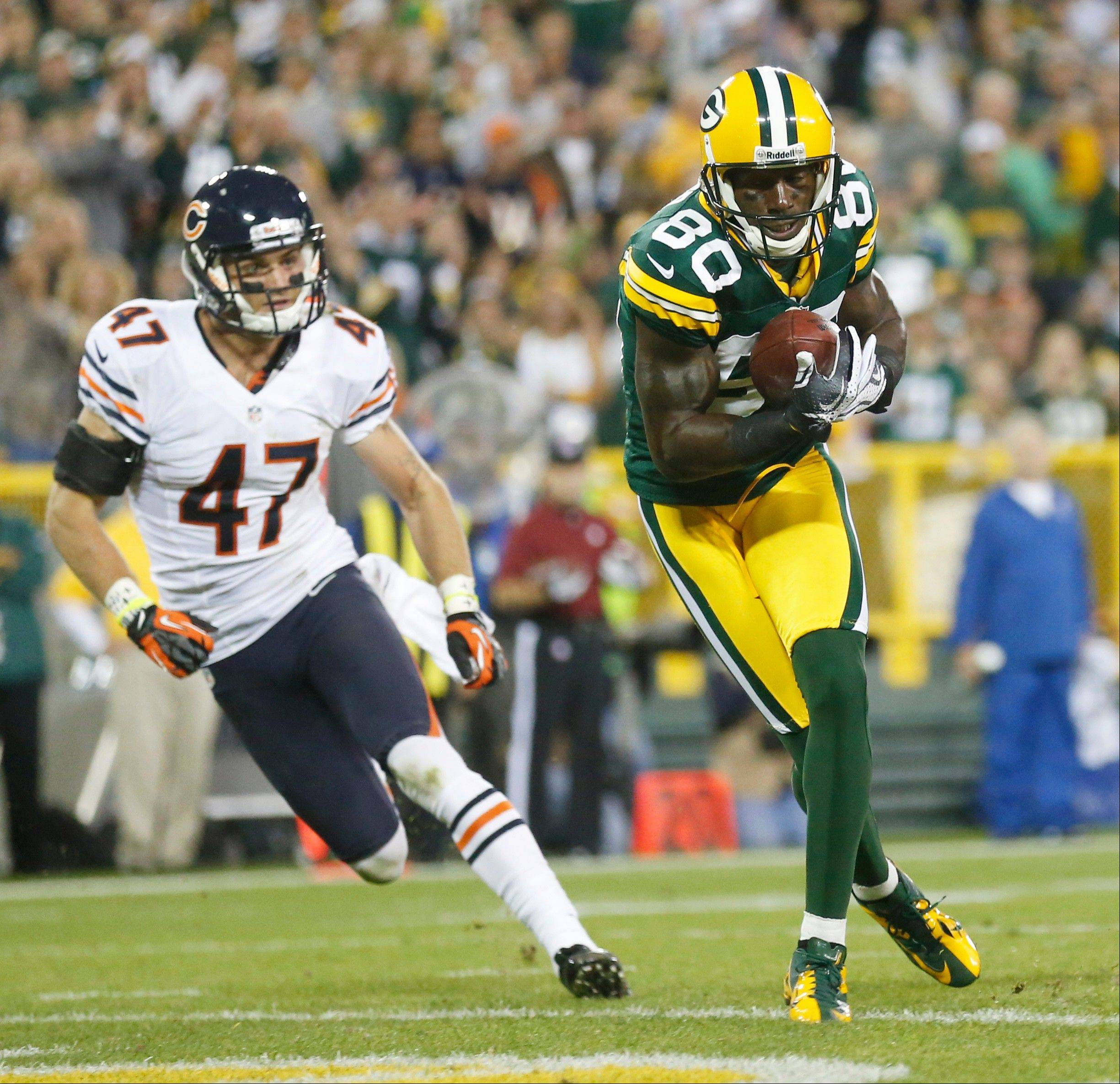 Green Bay Packers' Donald Driver catches a touchdown pass in front of Chicago Bears' Chris Conte during the second half.