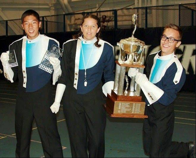 Accepting the Lancer Joust first-place trophy are the band's three drum majors, from left, Prospect High School junior Alex Yoo and seniors Destiny Duraj and Ted Marzolf.