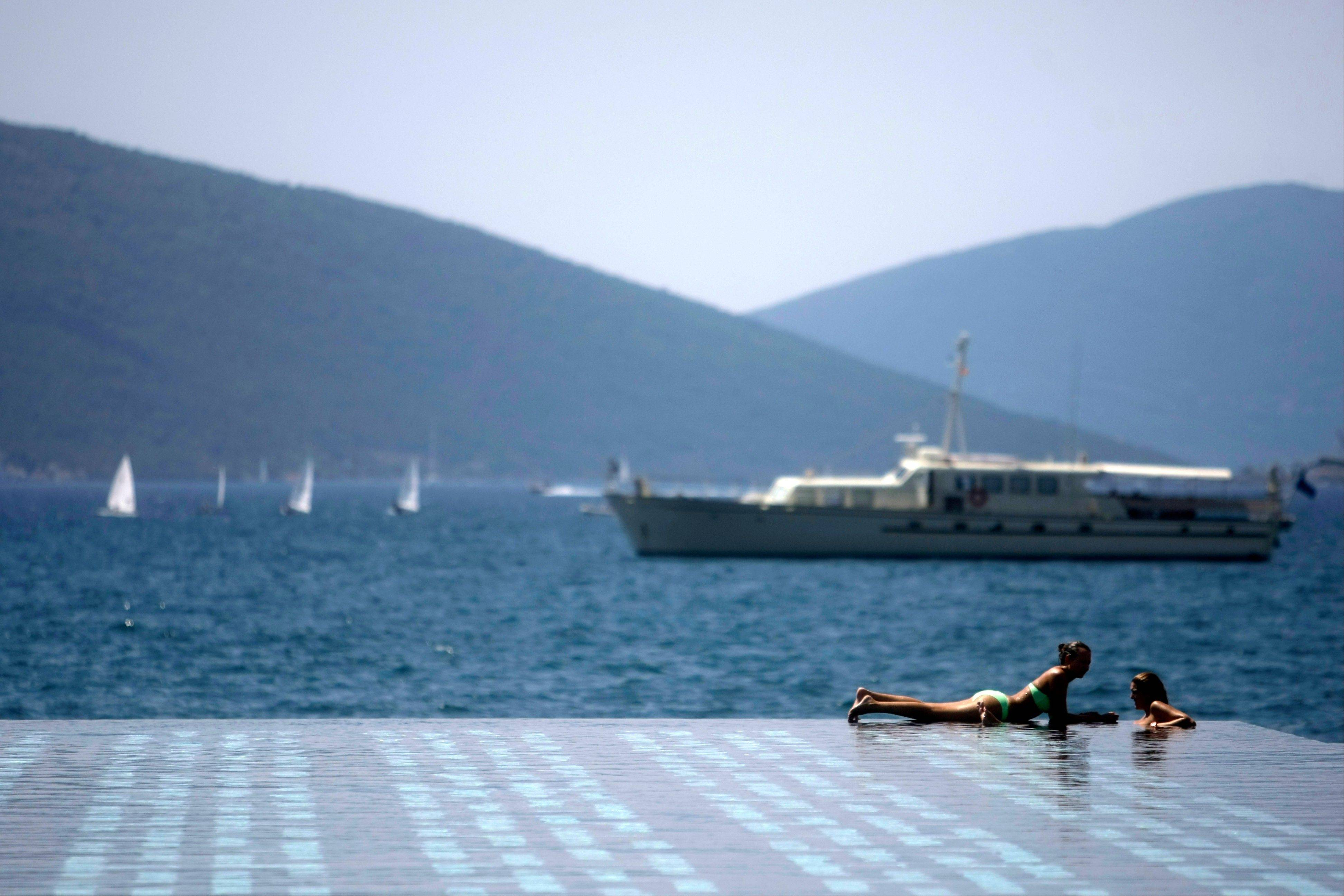 Two women sunbathe at the Porto Montenegro resort next to the town of Tivat in Montenegro.