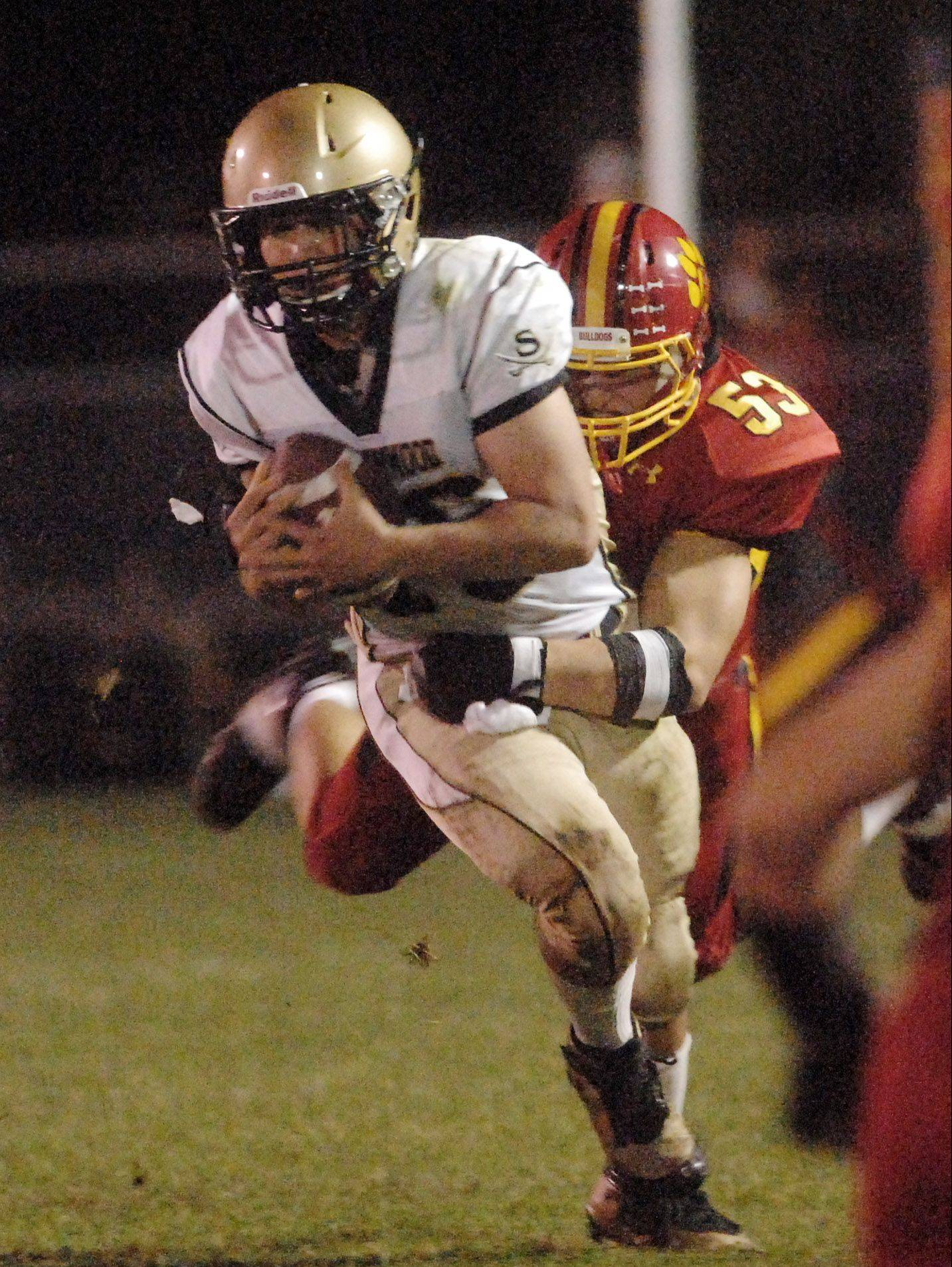 Batavia's Michael Gates brings down Streamwood quarterback Mason Polich Friday. The Bulldogs blanked the Sabres and allowed just 4 first downs.