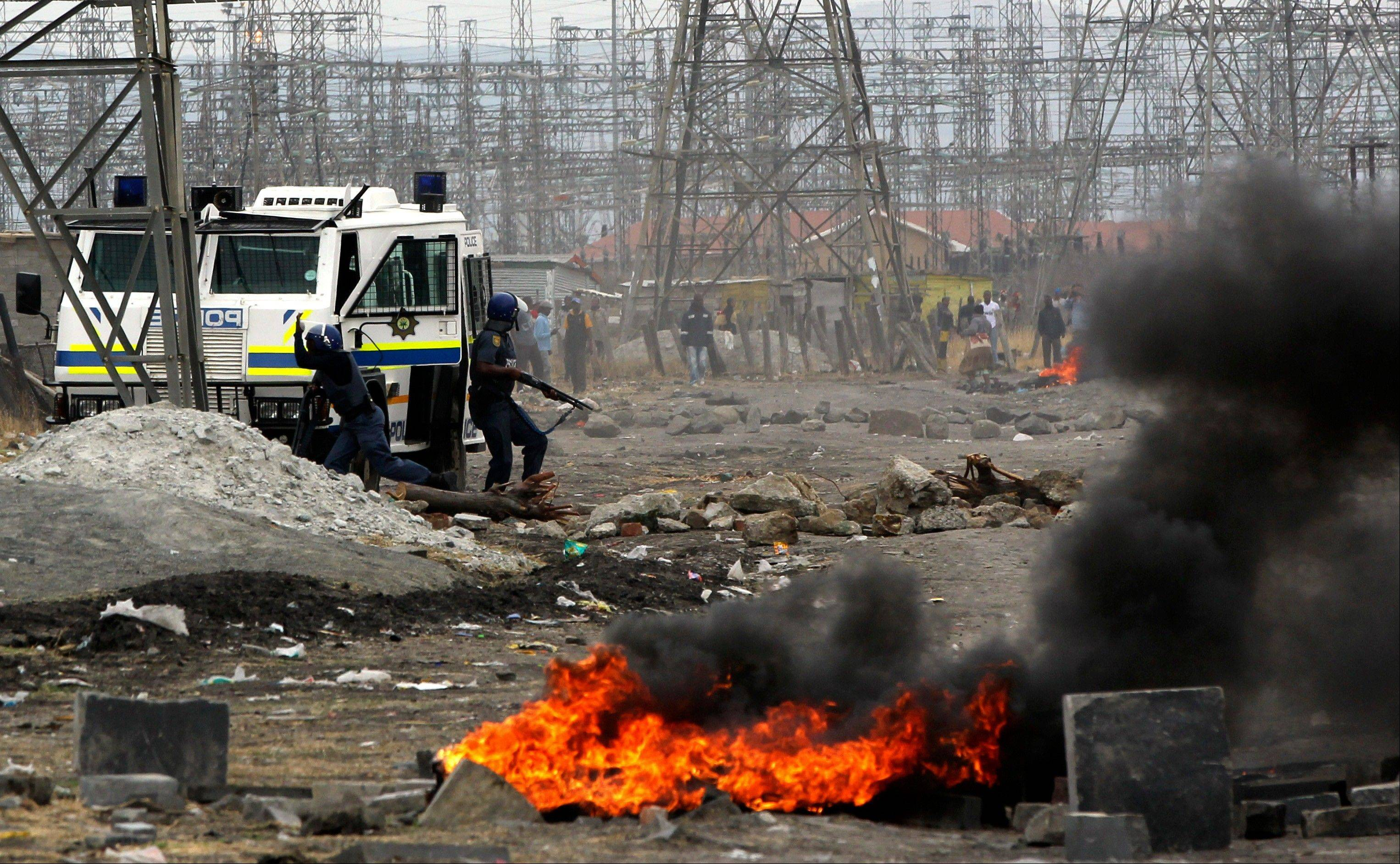 Police arrive Saturday as residents burn tires in Lonmin Platinum Mine near Rustenburg, South Africa.