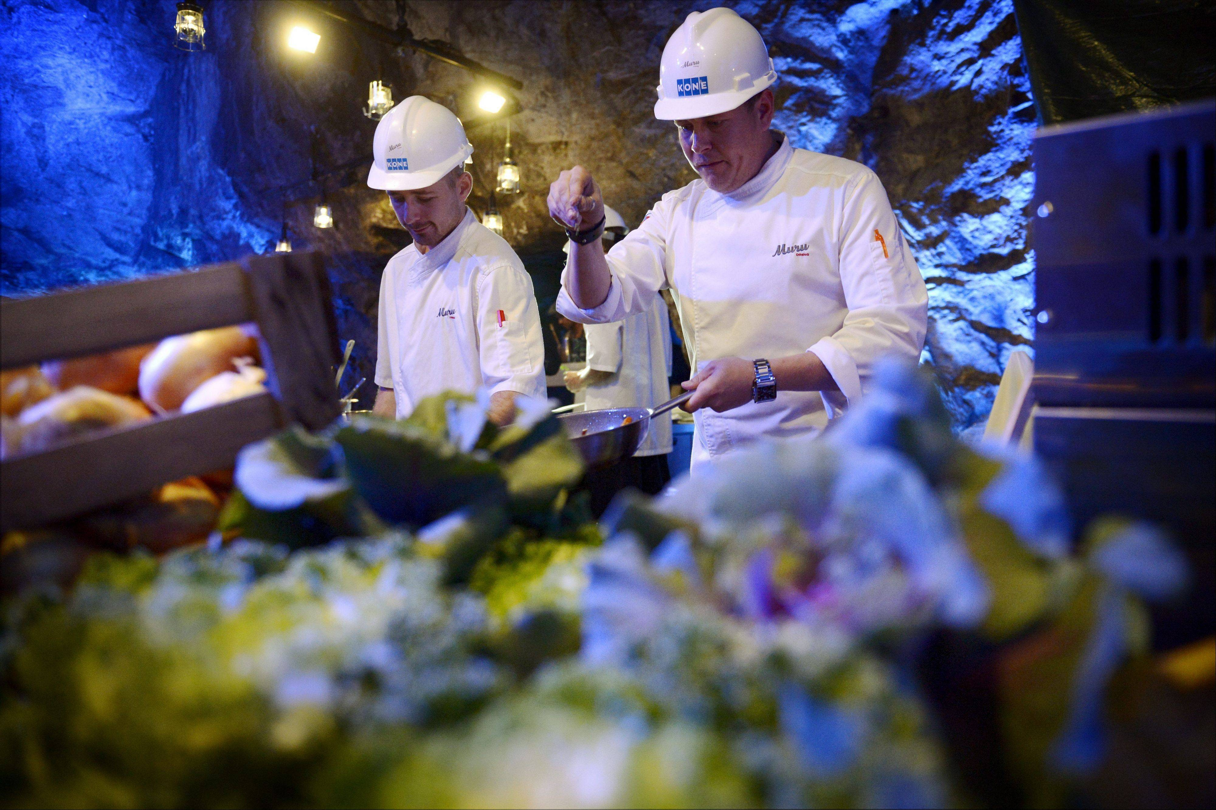 Chef Niklas Ekblom, left, and restaurateur Timo Linnamaki preparing food at Muru Pop Down restaurant at Tytyri mine in Lohja, Finland.