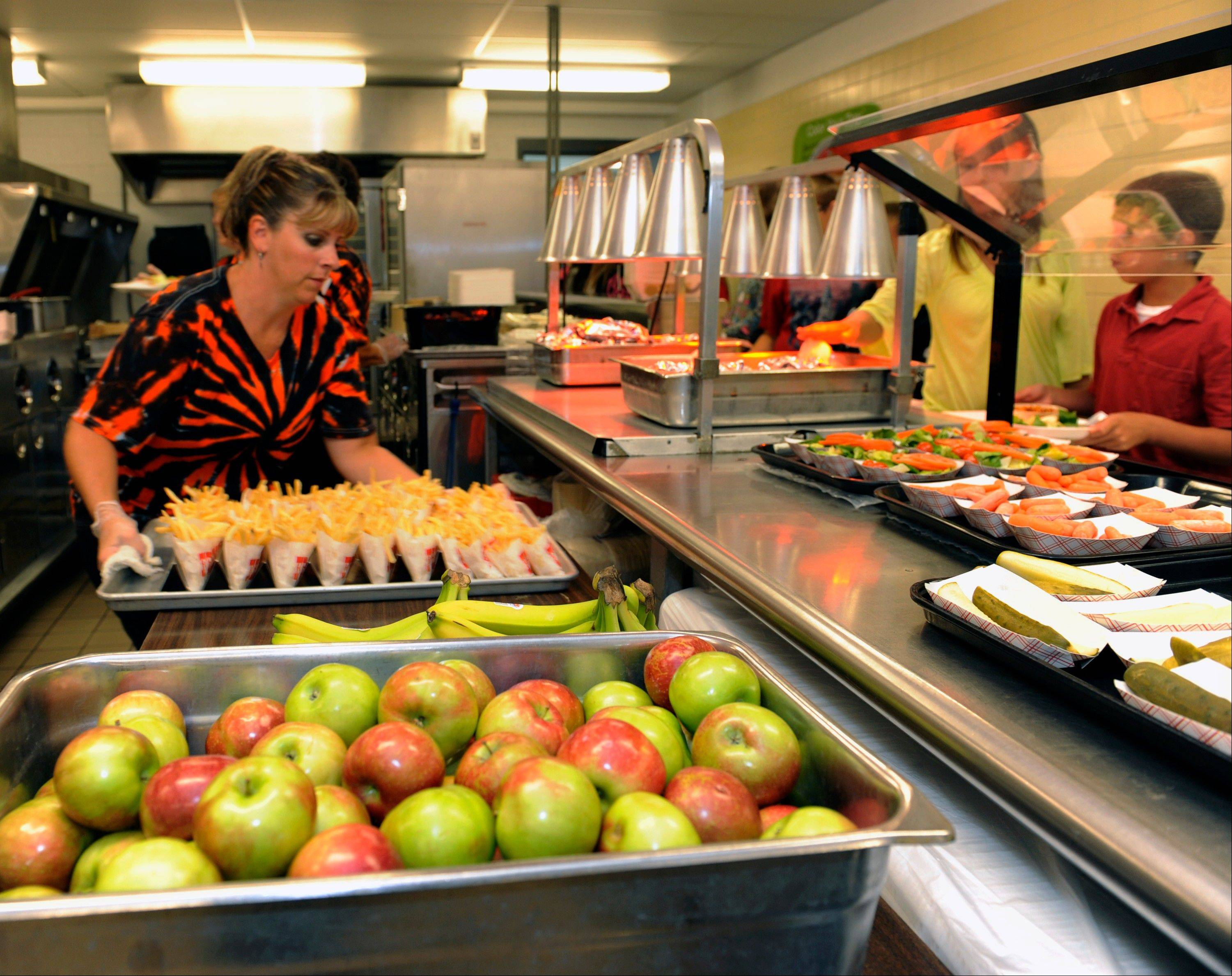 Michel Sasso, replenish's food items along the lunch line of the cafeteria at Draper Middle School in Rotterdam, N.Y., Tuesday, Sept. 11, 2012. The leaner, greener school lunches served under new federal standards are getting mixed grades from students.