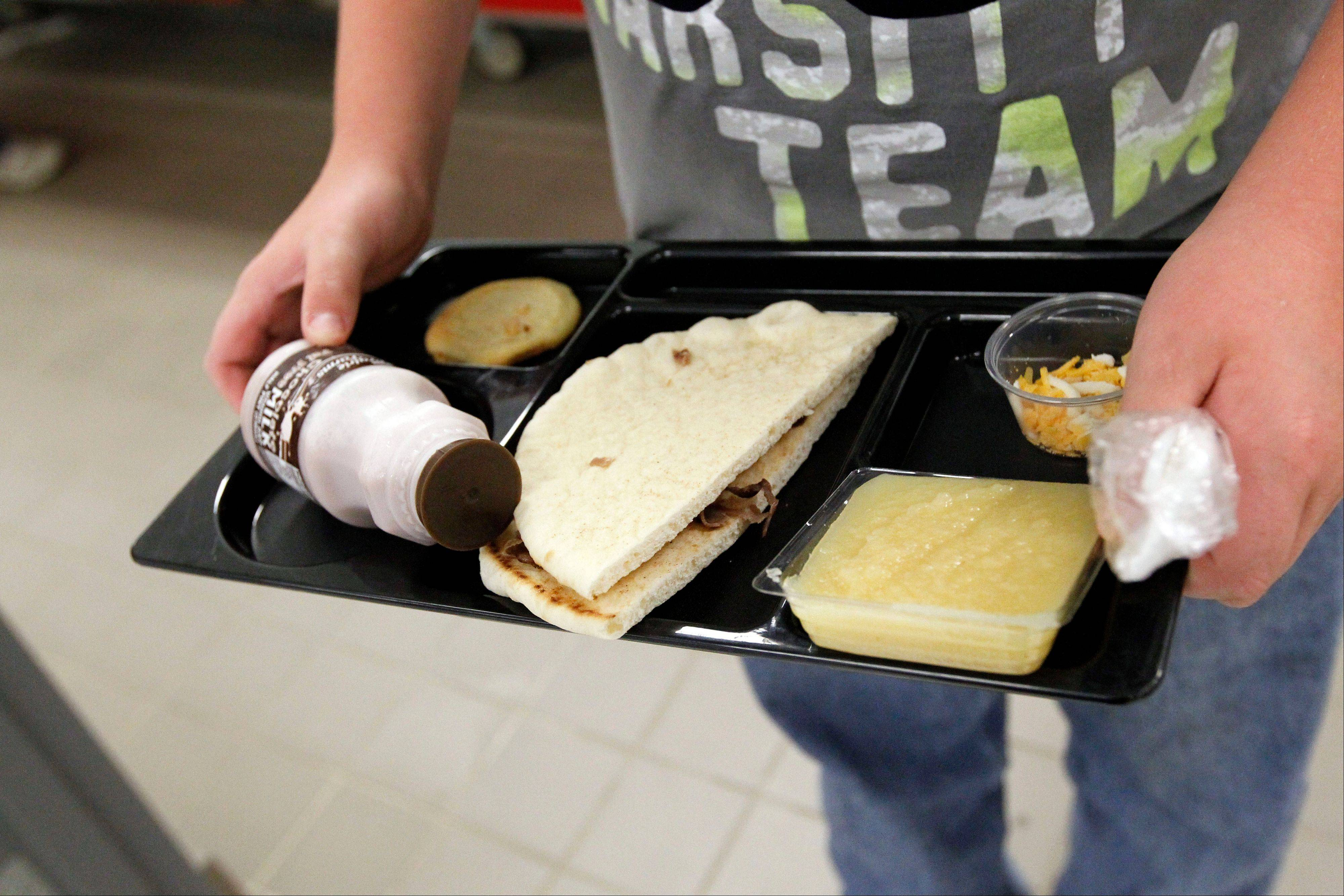 A student at Eastside Elementary School in Clinton, Miss., carries out a noon meal consisting of a flat bread roast beef sandwich, apple sauce, chocolate milk and a cookie, Wednesday, Sept. 12, 2012. The leaner, greener school lunches served under new federal standards are getting mixed grades from students.