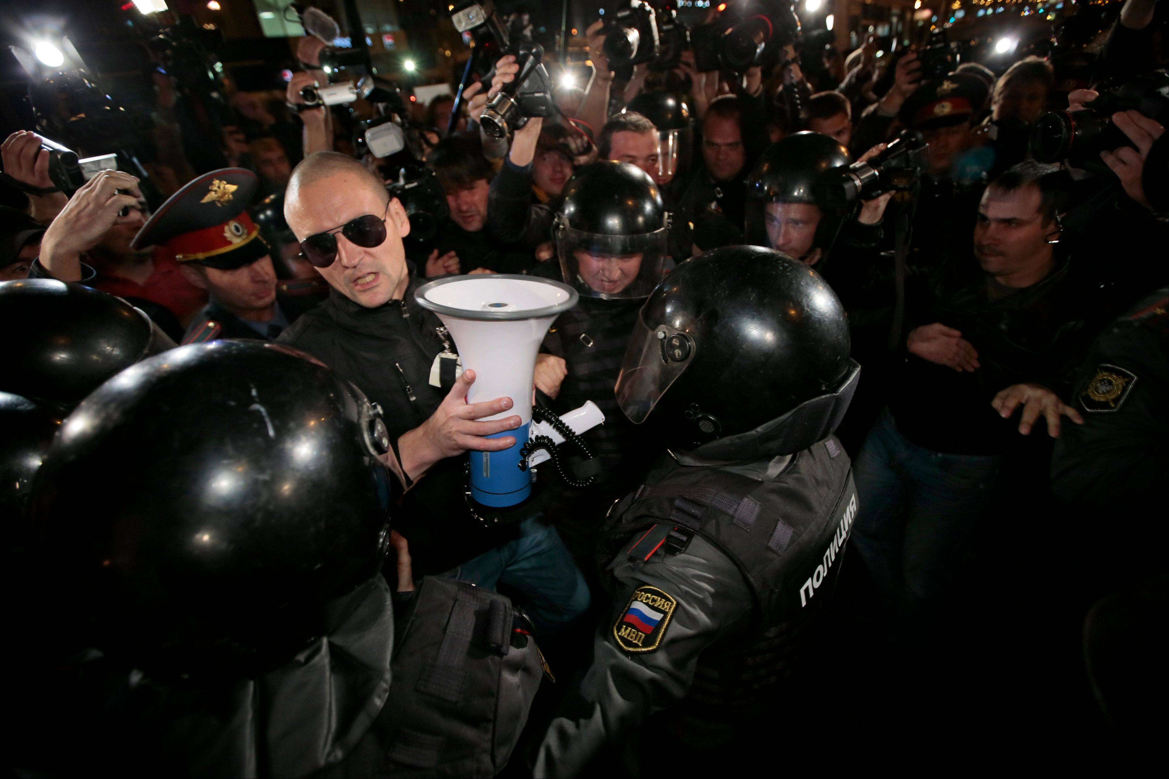 Police officers detain opposition leader Sergei Udaltsov, in sunglasses, after a protest rally Saturday in Moscow.