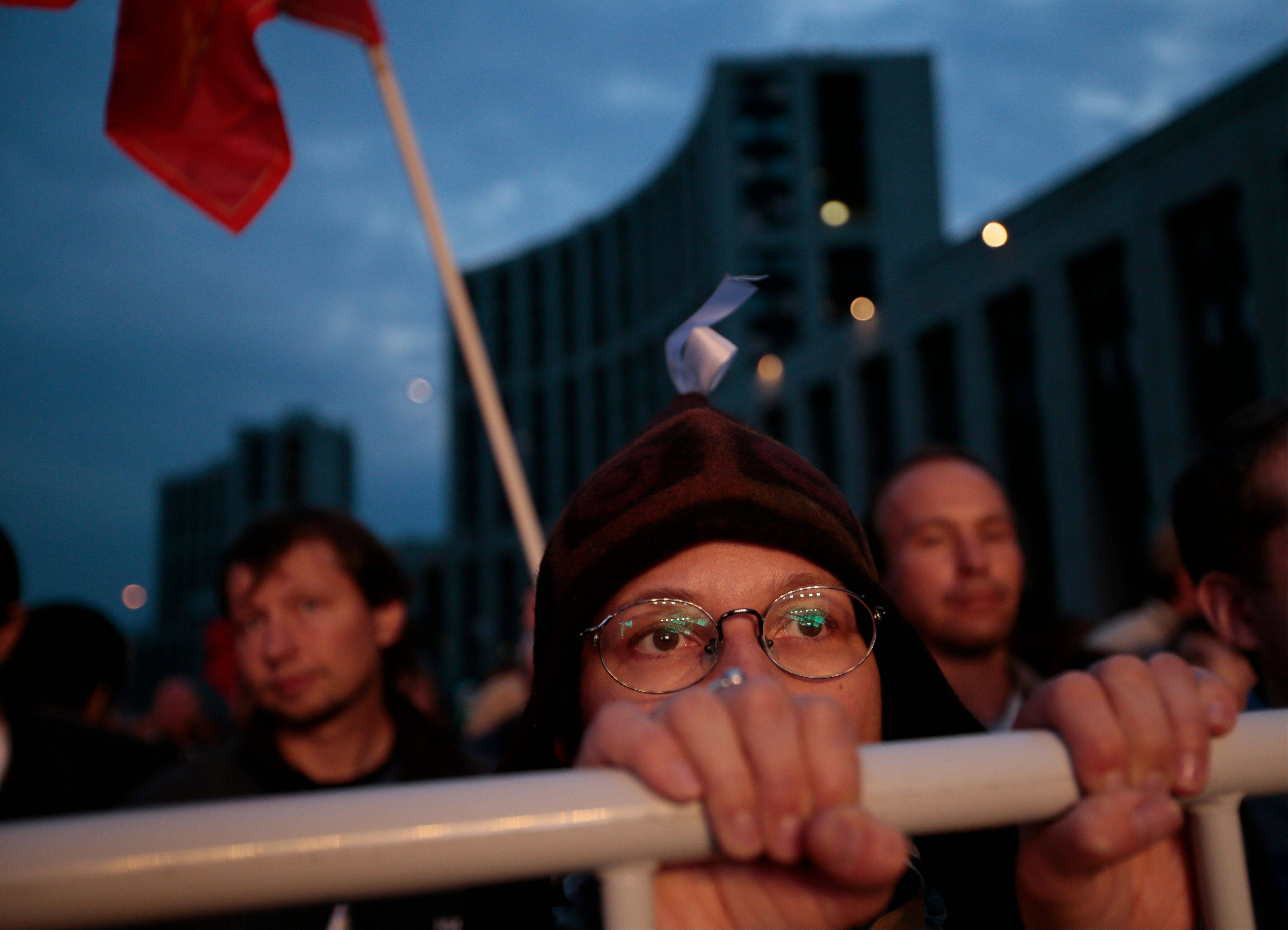 An opposition protester listens to an orator Saturday during a protest rally in Moscow.