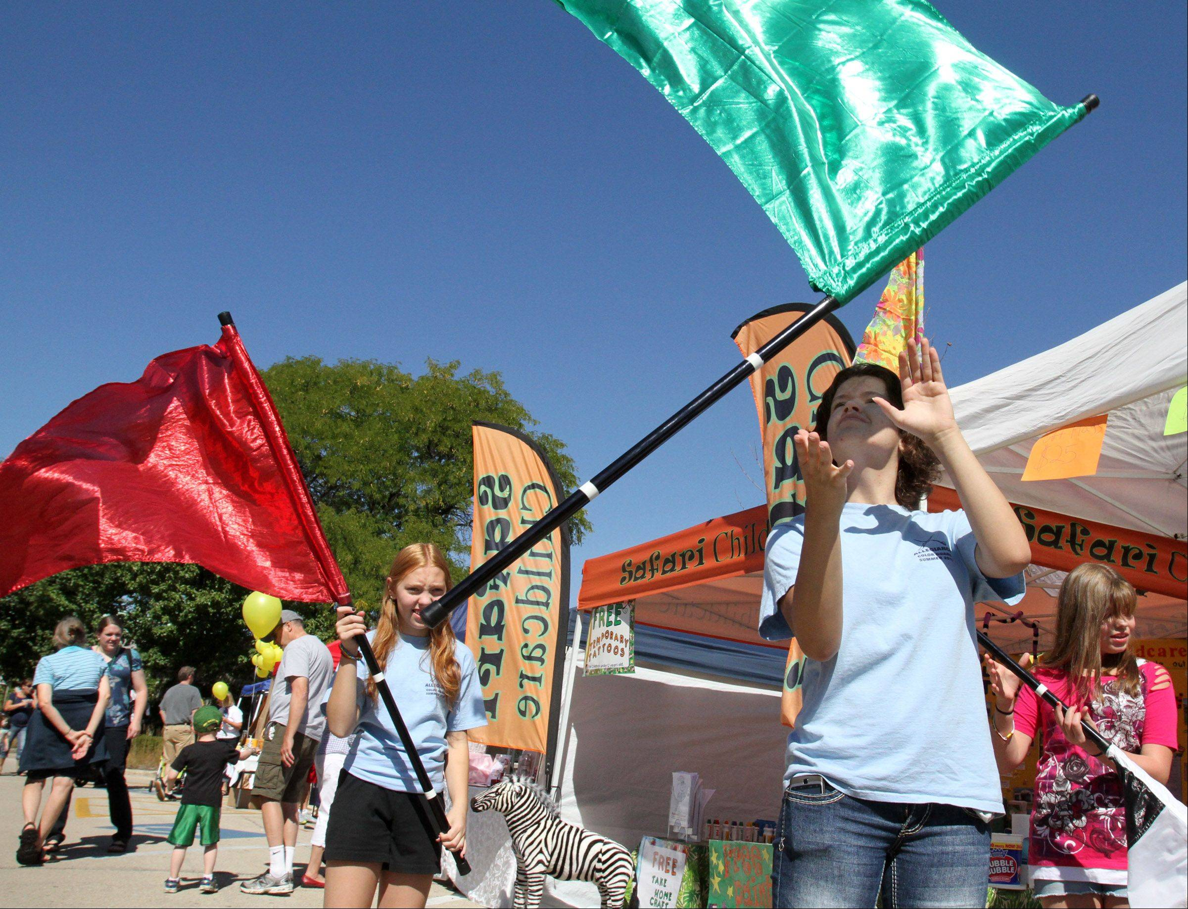 Kristin Ward, 16, center, Amber Thurn, 12, left, both of Carpentersville, and Patricia Quill, 12, of West Dundee, right, with Allegiance Color Guard demonstrate flags at the businesses booth on Saturday during Heritage Fest in West Dundee.