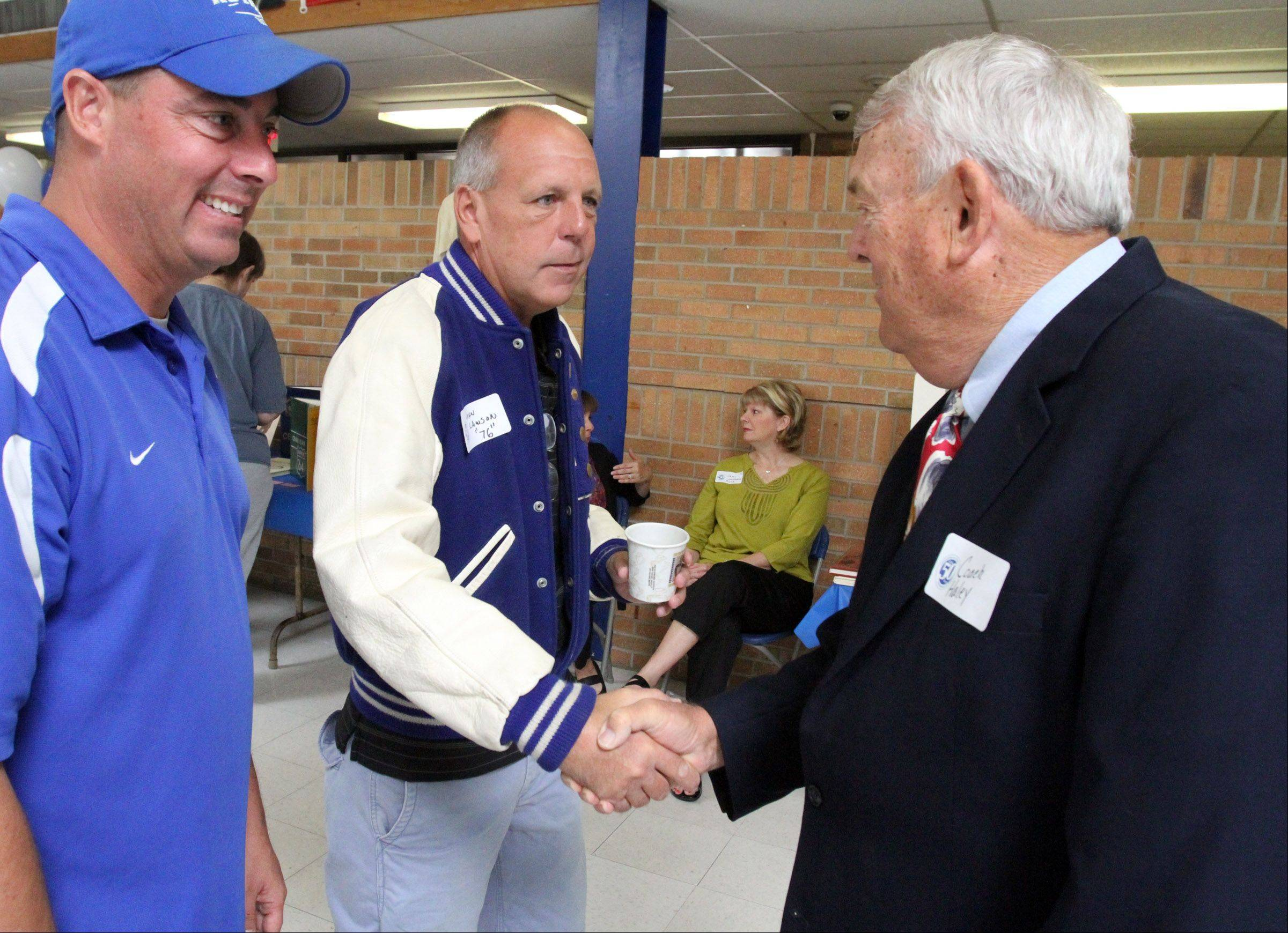 John Lawson, a 1976 graduate of Larkin High School in Elgin, center, greets coach Ray Haley, who was Larkin High School's first athletic director and longtime varsity football coach. With them is current varsity coach Mike Scianna, left. The group took part in Larkin's 50th anniversary open house on Saturday.