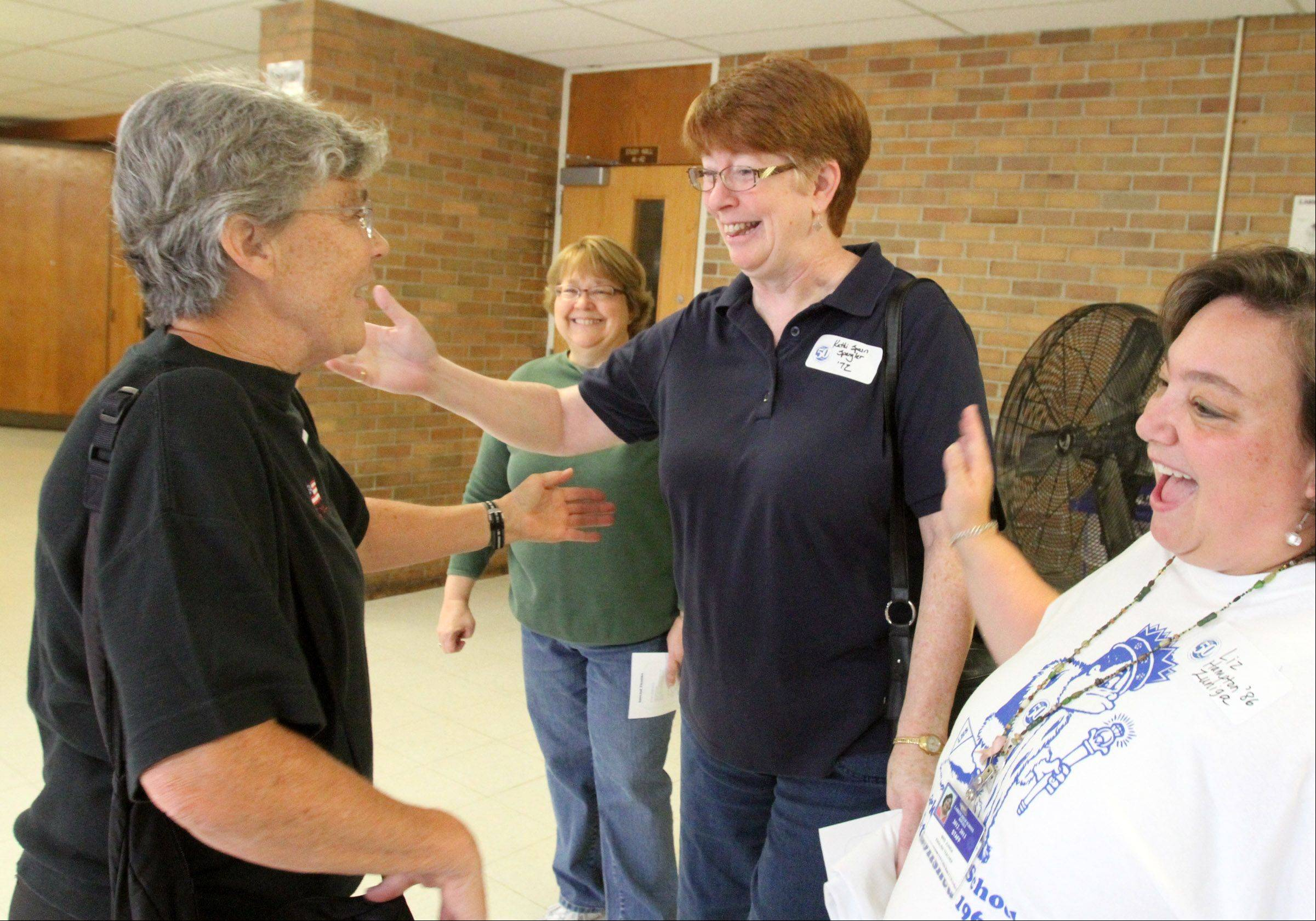 Mary O'Brien, a former 34-year teacher and 27-year varsity girls volleyball coach at Larkin High School, left, is greeted by 1972 graduate Kati Spangler, center, and 1986 graduate and 22-year Larkin English teacher, Liz Zuniga, right, during Larkin High School's 50th birthday open house in Elgin on Saturday.